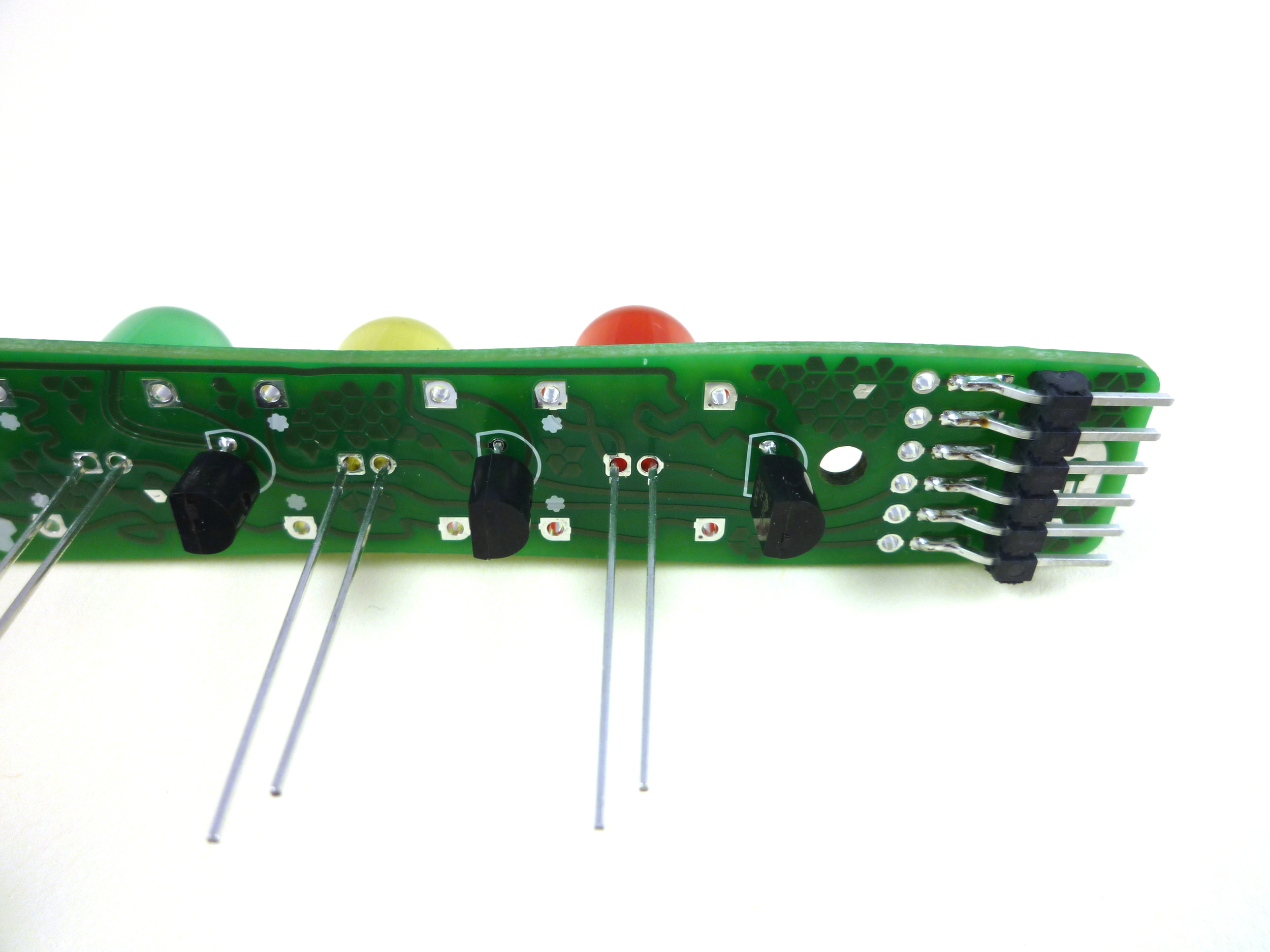Insert the LEDs to their sockets. It doesn't matter which LED colour goes where,  but the long leg of the LED must go into the square hole ! Make sure that the LED's base sits right against the board and solder all of them into place. Clip the leads.