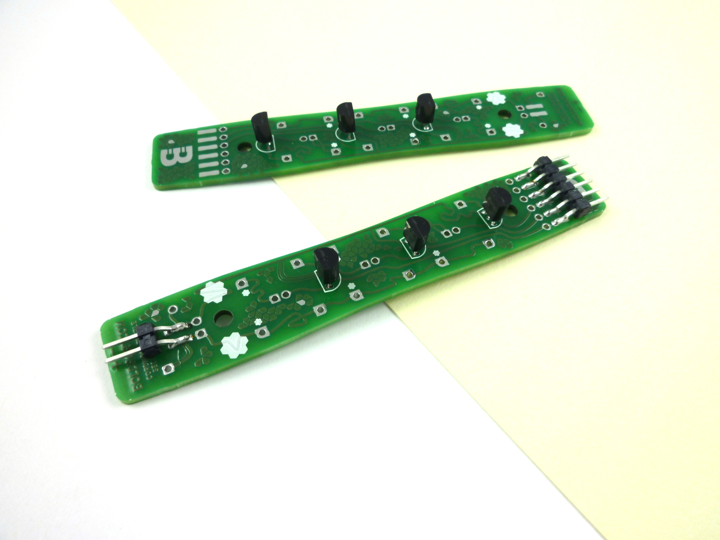 On to one of the boards solder both the 2-pin and 6-pin header, making  sure that the tips are flush with the circuit board's edge.