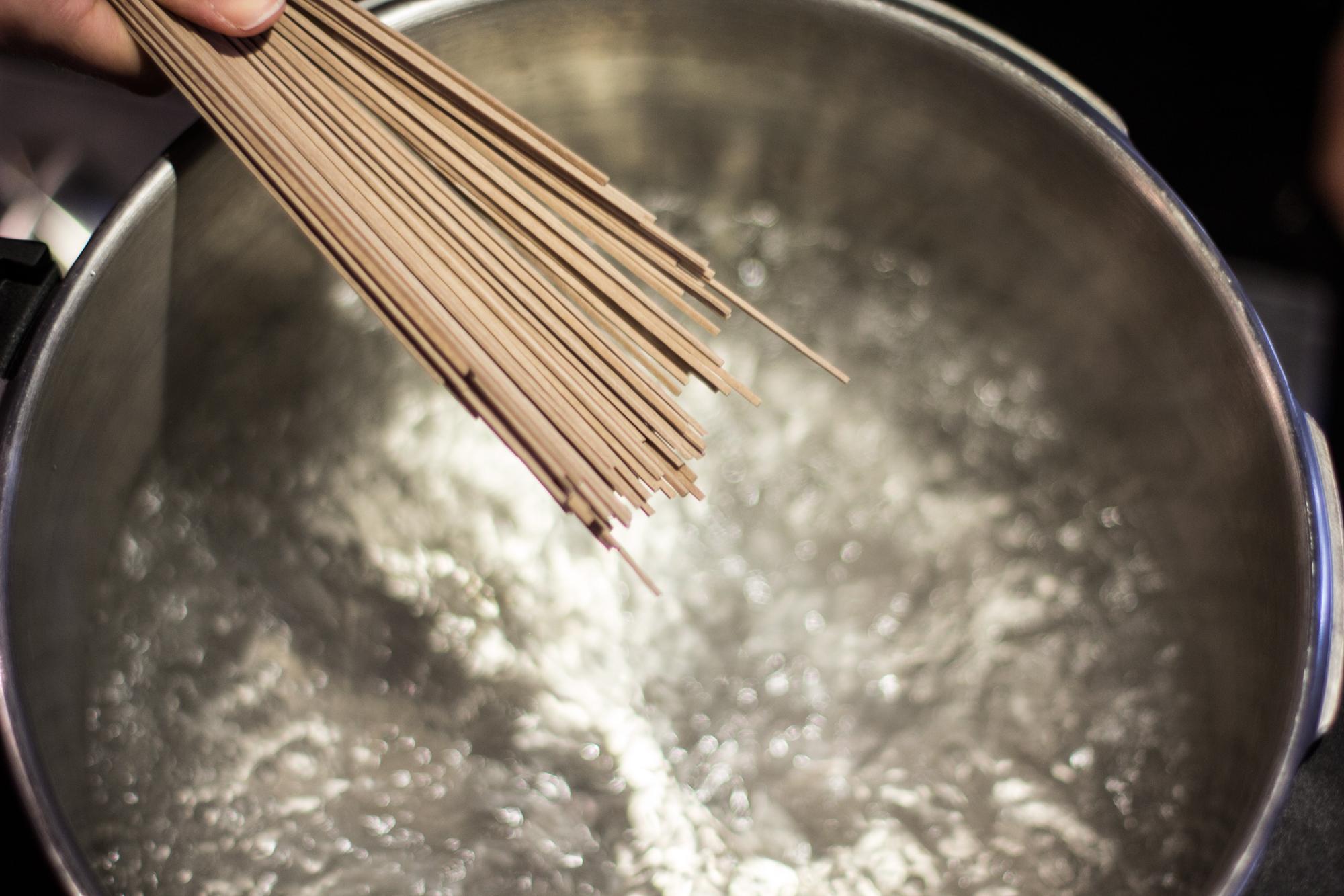 Boiling soba noodles.