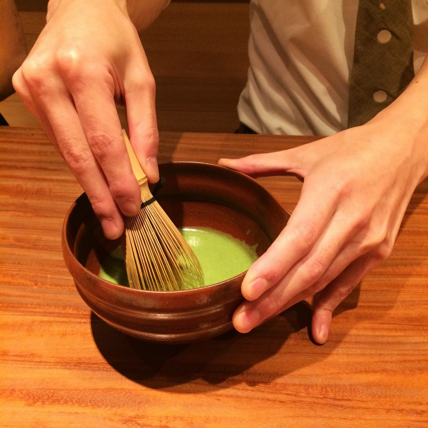 Making matcha tea using a special bamboo whisk known as a chasen.