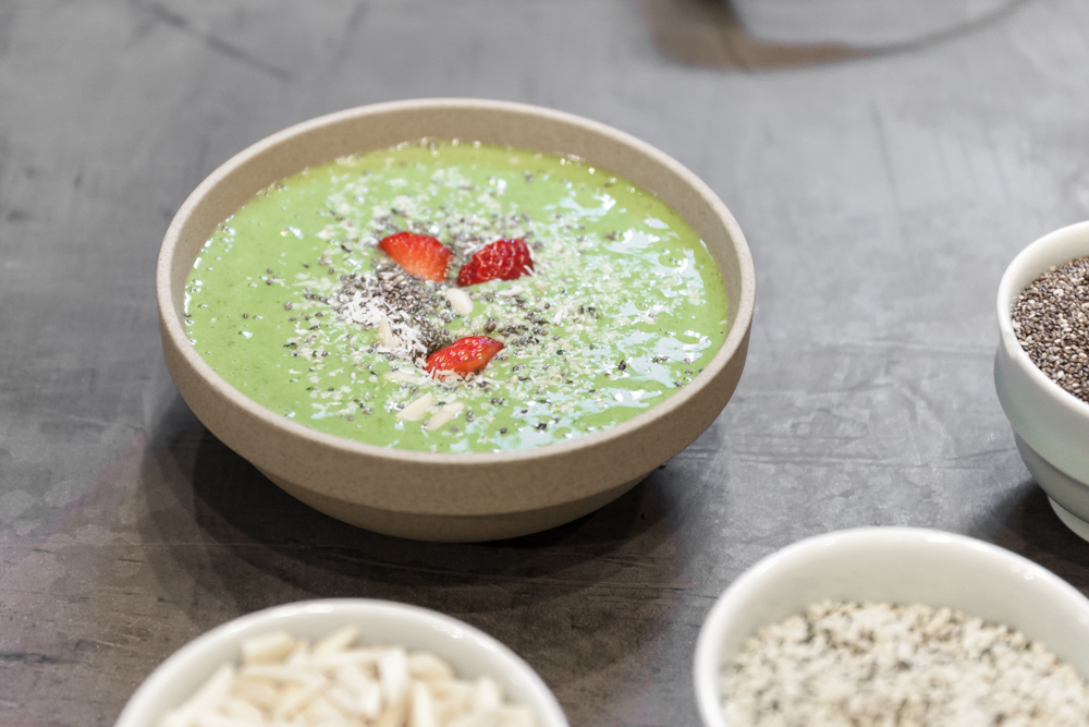 A matcha smoothie bowl with chia seeds, strawberries, cashews, and coconut shavings.