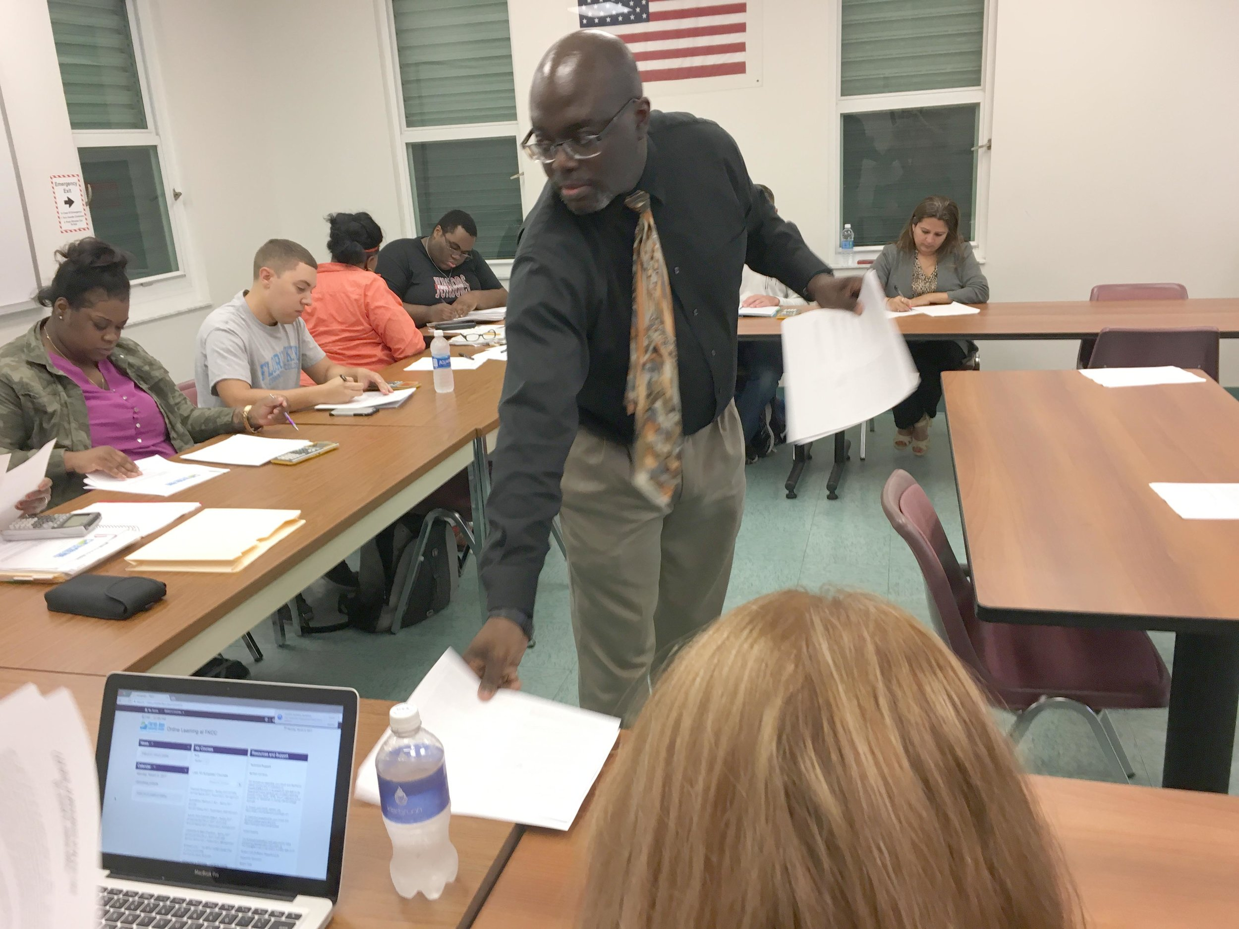 Professor Jemal Alston — better known as Dr. J — hands out a syllabus to a financial management class at Florida Keys Community College. Photo by Nancy Klingener