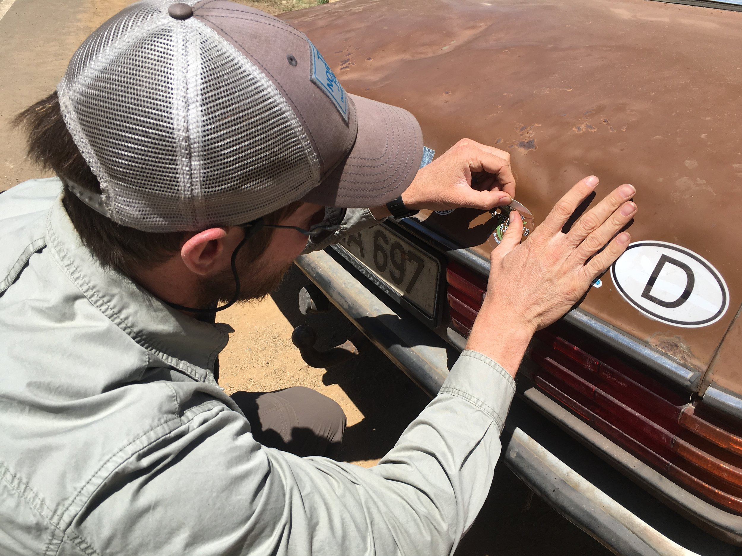 Isaac applies an Overland Expo decal at Blue's request. This will be the final addition before the Benz is entombed in a museum.