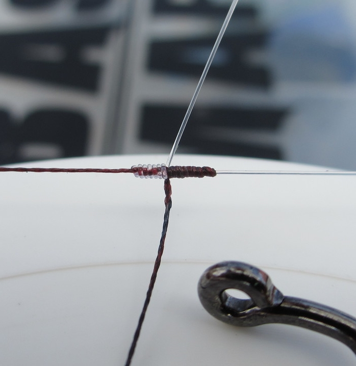 """6 lb fluorocarbon tied to 15 lb braided line with a modified blood knot (7 wraps on the fluorocarbon, 11 wraps on the braid) Shown with a worm hook eyelet for size comparison. Truly a """"micro"""" knot."""