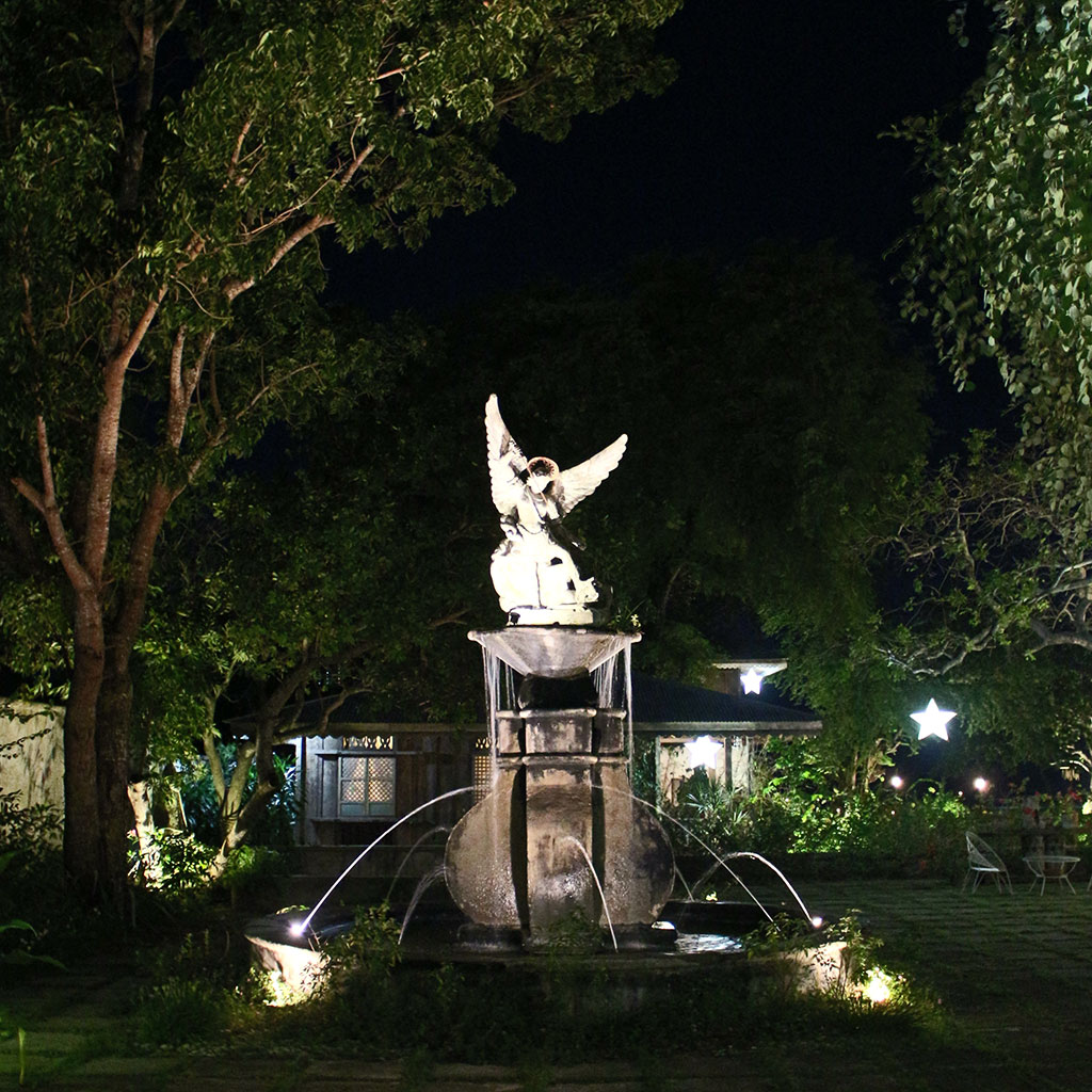 A magnificent water fountain with a statue of an angel at night in Sitio Remedios Heritage Village.