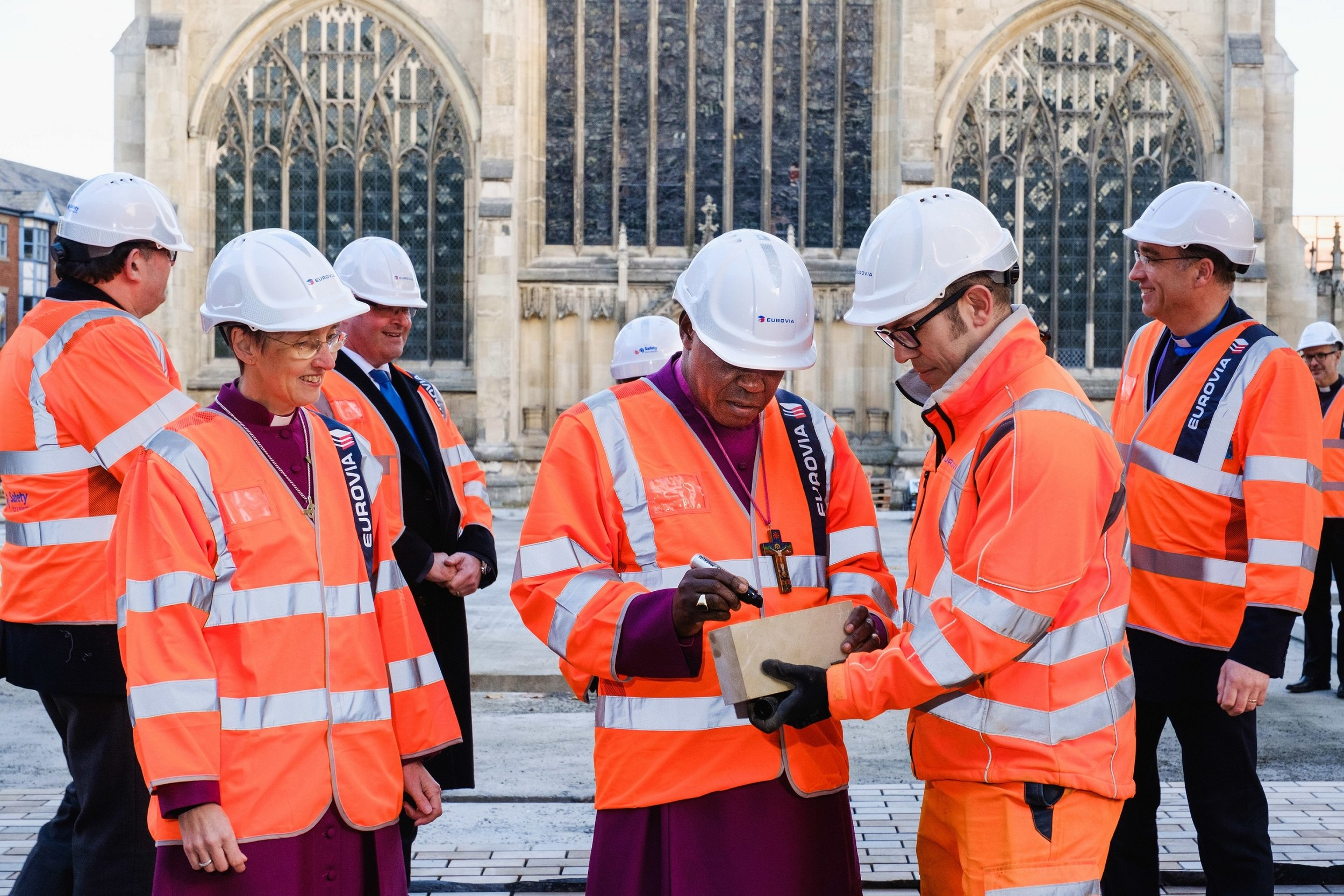 The Archbishop signs a paving stone in the presence of the Bishop of Hull, the Right Reverend Alison White, and Tim Croft, Site Manager for the Trinity Square works being delivered by contractors Eurovia Contracting.