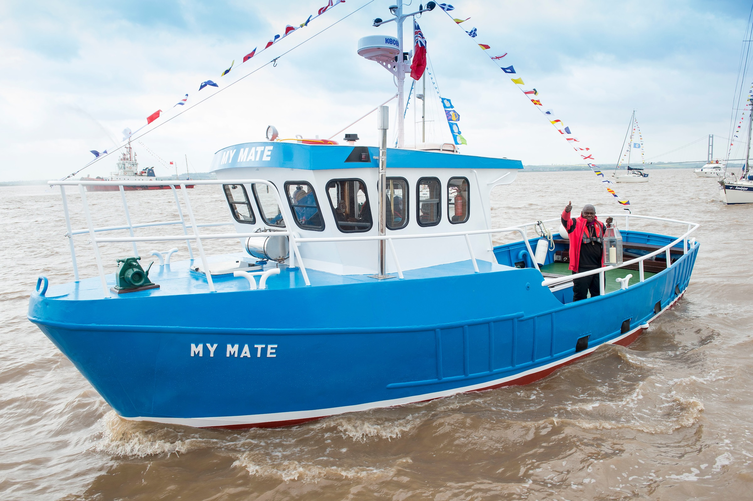 The Archbishop carries a lantern from All Saints Church on board the trawler My Mate at the head of a flotilla of vessels on the Humber estuary.