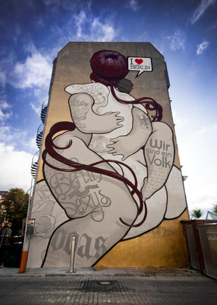 Dos amantes tatuados, con símbolos del oeste uno, del este el otro, se funden en un abrazo. Homenaje al diálogo y entendimiento pintado frente a los restos del viejo muro en el 20º aniversario de la caída.