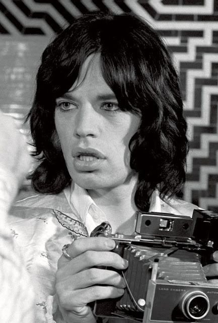 Mick Jagger with a Polaroid. Image by Baron Wolman.