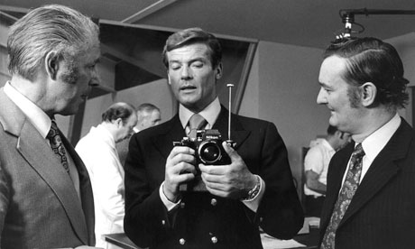 Roger Moore's James Bond (centre) checks out a camera rocket launcher in the 1974 film The Man With the Golden Gun. Photograph- Allstar/Cinetext Collection/Sportsphoto