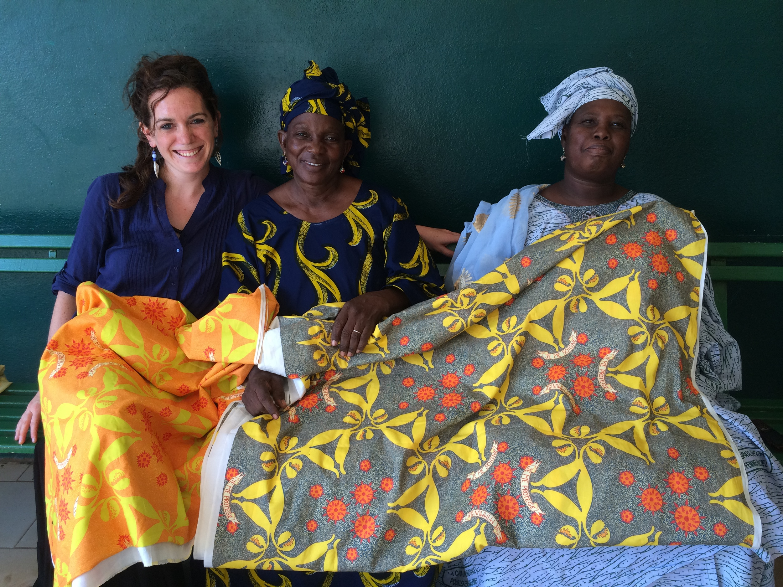 "GAIA Vaccine Foundation Executive Director, Eliza Squibb, with Mme Rokia Sangare and Madame Fatoumata Diarra showing off the HPV ""story-telling cloth"" design at the Hope Clinic, a project funded by the foundation in Bamako, Mali."