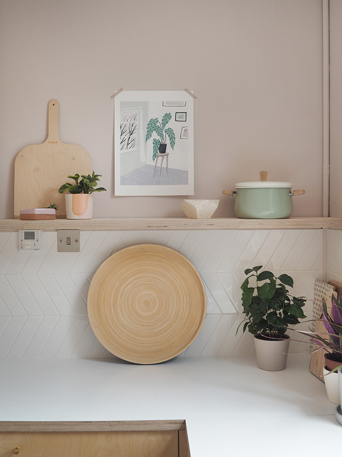 Wooden chopping board on shelf is from  Baileys ; the plant pot just in front of the board is by  Oh Happy Glaze ; the other ceramic pieces on the shelf I bought in Mexico City. Print on the wall is by  Fran Murphy ; pot on the right is from  Ikea ; the large round tray is from  Feather & Nest *.
