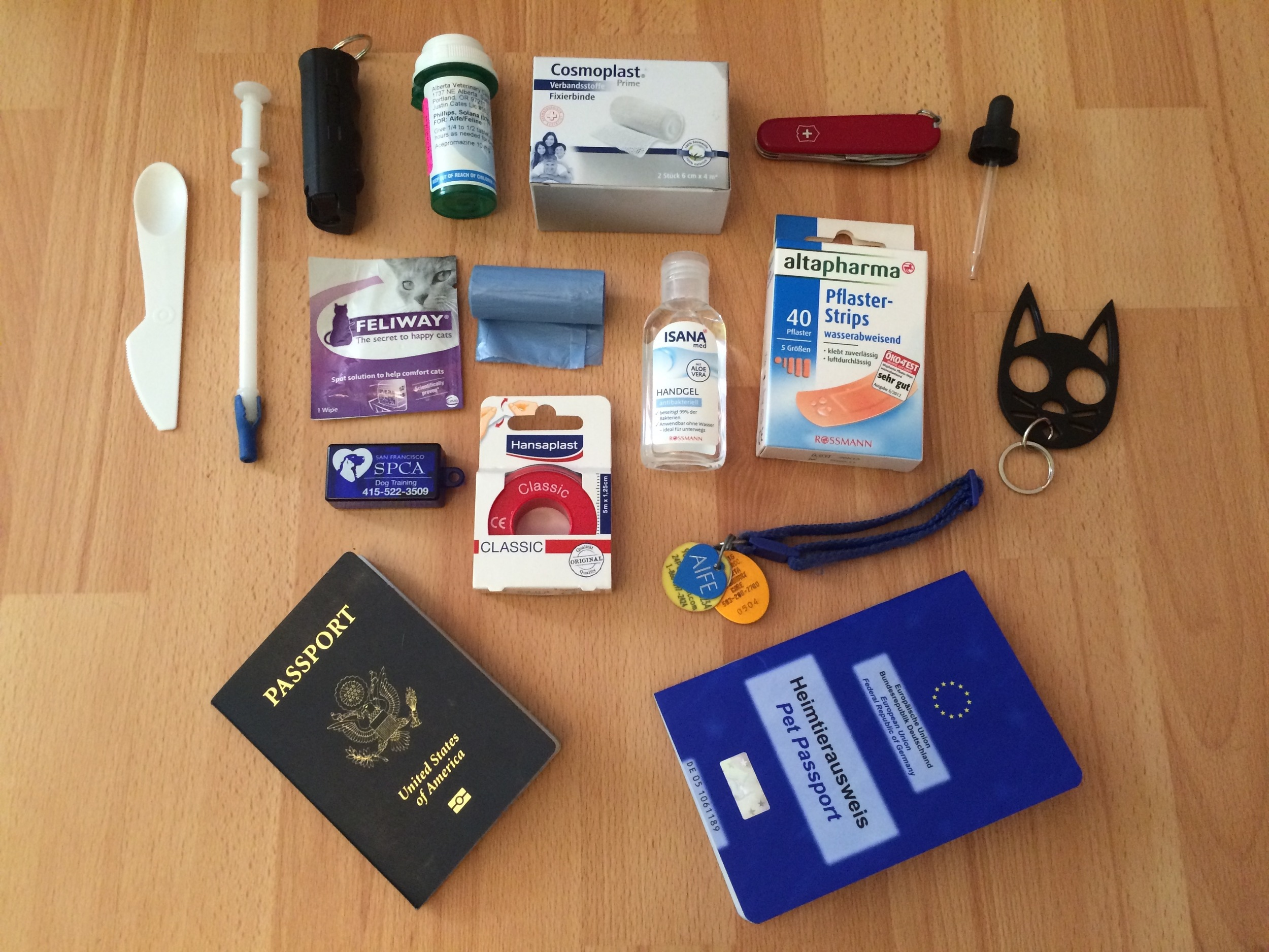 Some of the emergency cat-schlepping supplies we have collected: pepper spray, emergency sedatives, hand sanitized, pill-dropper, eye-dropper, cat-shaped shanking keychain, bandages, calming pheromone wipes, training clicker, rabies license & microchip tags, passports (human + cat)