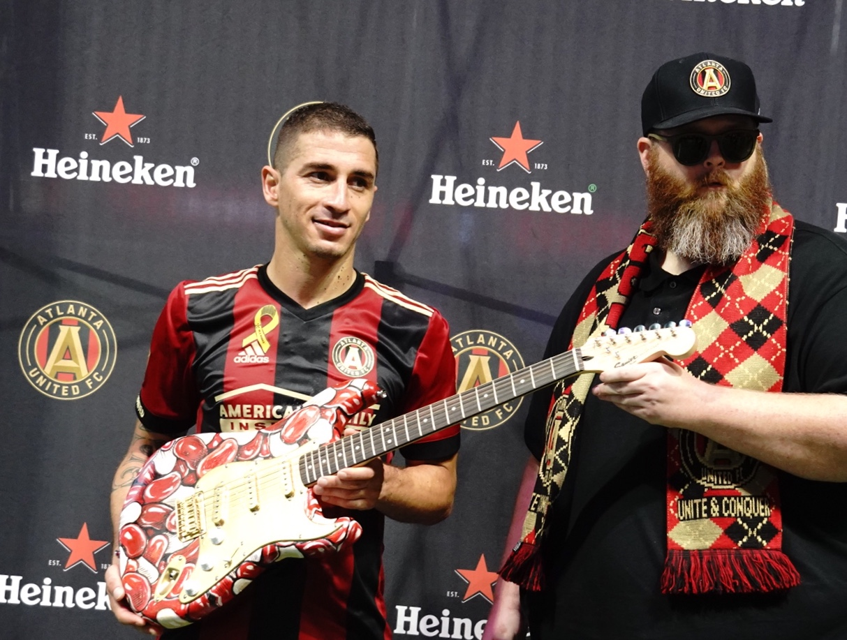 "2017- on field with ATLUTD's Carlos Carmona at Mercedes-Benz Stadium, with Custom Painted Guitar for Heineken's Man of The Match.     Jeremy Townsend   b. 1977, St.Louis, Mo, Usa  Pseudonymns: Jert; Mister Jert     Jeremy Townsend was born in 1977 to a working class family in Jefferson County, Missouri.      He began using the pseudonym ""Jert"" at age 16 (1994).      The pseudonym stuck because it sounded weird and was easy for people to remember.     At age 20 he discovered the world of live caricature art - and found a means to support himself and travel across the US and Europe without a trust fund.      In 2008 he abandoned full time caricature to focus on freelance illustration and independent creative projects.     Since then he has shown work vigorously in galleries, group shows and alternative spaces across the US.      He is currently focusing his efforts on cultural satire and pop culture iconography.     He lives in the Atlanta Metro area with his wife and dogs.     Education:   AFA- STLCC Meramec- 1999  Sebastian Kruger Acrylic workshop - Garmisch-Partenkirken, Germany-2006  Sebastian Kruger Acrylic workshop-  St.Goar, Germany-2007  Sebastian Kruger Acrylic workshop  Barsringhausen, Germany-2008  Sebastian Kruger Acrylic workshop  Santa Barbara, California -2010     Selected Shows:  Cryptids-   2015, Kibbie Gallery; Atlanta, GA  w/Aaron Crawford, Chris Neuenschwander      …War Against Boredom-   2013, Mad Art Gallery; St. Louis, Mo  w/ Aaron Partney     Death and Girls…  2012, Cube Gallery: Atlanta,GA  w/ Eric Petersen     Socially Awkward-  2012, Mad Art Gallery: St. Louis, Mo  w/ Ron Buechel        Selected Group Shows:  This is it!-  2017, Blue Mark Studios: Atlanta Ga     Trumpocalypse- What Next?  2017, Sacred Gallery: New York, NY     Dumping Trump: Art Against the Donald  2016, Elephant Room Gallery; Chicago, Ill.     South-  2015, Kibbee Gallery; Atlanta, GA     Mr.Show Show-  2014, Nerdist Gallery, Meltdown comics, Los Angeles, CA     ICONS-  2013, Thee Grotto- Alternative Space  Orlando, Fl     Born and Bred  2013, ABV Gallery, Atlanta, GA     Grey Scale  2012, ABV Gallery, Atlanta, GA     Difference and Discourse  2010, Keyhole Gallery, Kansas City, MO     World of Imagination vol.3  2010- APW Gallery; New York, NY     Lost Toys  2010- Mercer Gallery; Rochester NY     Golden Age- Asifa Atlanta group show  2008- Eyedrum Gallery; Atlanta Ga           Curated shows:  People Ruined the Internet  2015, HodgePodge- Alternative Space; Atlanta GA        Lectures:  Art of Caricature- 2009- SCAD ; Savannah, GA, Illustration Building     Art of Caricature- 2010- SCAD; Savannah, GA, Illustration Building     Art of Caricature vs the Act of Caricature-2014- ISCA annual convention; Reno NV     Press:     Interview by Ali Thome from episode 14 of the ""It's Supposed to Be Funny"" podcast  http://www.itssupposedtobefunny.com/14-mr-jert/     Jert Says 'People Ruined The Internet'- Creative Loafing- Kate Douds- 2015-  http://www.creativeloafing.com/news/article/13082427/jert-says-people-ruined-the-internet       Who is Jert?-  13thflr.com -  Gavin Godfrey- 2013-   https://13thflr.com/tag/jert/      10 Best Shows This Weekend in St.Louis- Riverfront Times- Mabel Suen- 2013 -  https://m.riverfronttimes.com/musicblog/2013/07/12/the-ten-best-shows-in-st-louis-this-weekend-july-12-to-14      Published works:  ""Secret Lives of Cellphones"" - 39 page comic in ""Satellites: a Comics Anthology"", 2015- Art Squared Publishing     Awards:  C4 (California Comics Cartoon & Caricature Convention) - ARTIST OF THE YEAR- 2007- San Diego, CA     4 time ISCA top 10 caricaturist in the world  2005  2009  2011  2013     4 time ISCA Most Humorous artist  2006  2008  2009  2011     2005 ISCA guest of honor award for outstanding work     Secret Walls record: 4-3     Collections:  ""Portrait of Luke The Drifter""   18 X24  Watercolor and Ink on Paper  Hank Williams Museum, Montgomery Alabama           Twitter- @mrjert  Instagram: @mrjert  Facebook: /misterjert"