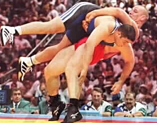 "Consensus best International Male Wrestler of all time, Aleksandr Karelin (red), executes his signature ""reverse lift"". 27 International Golds, one Silver, 13 year unbeaten streak (six years unscored on), 887-2 career record."