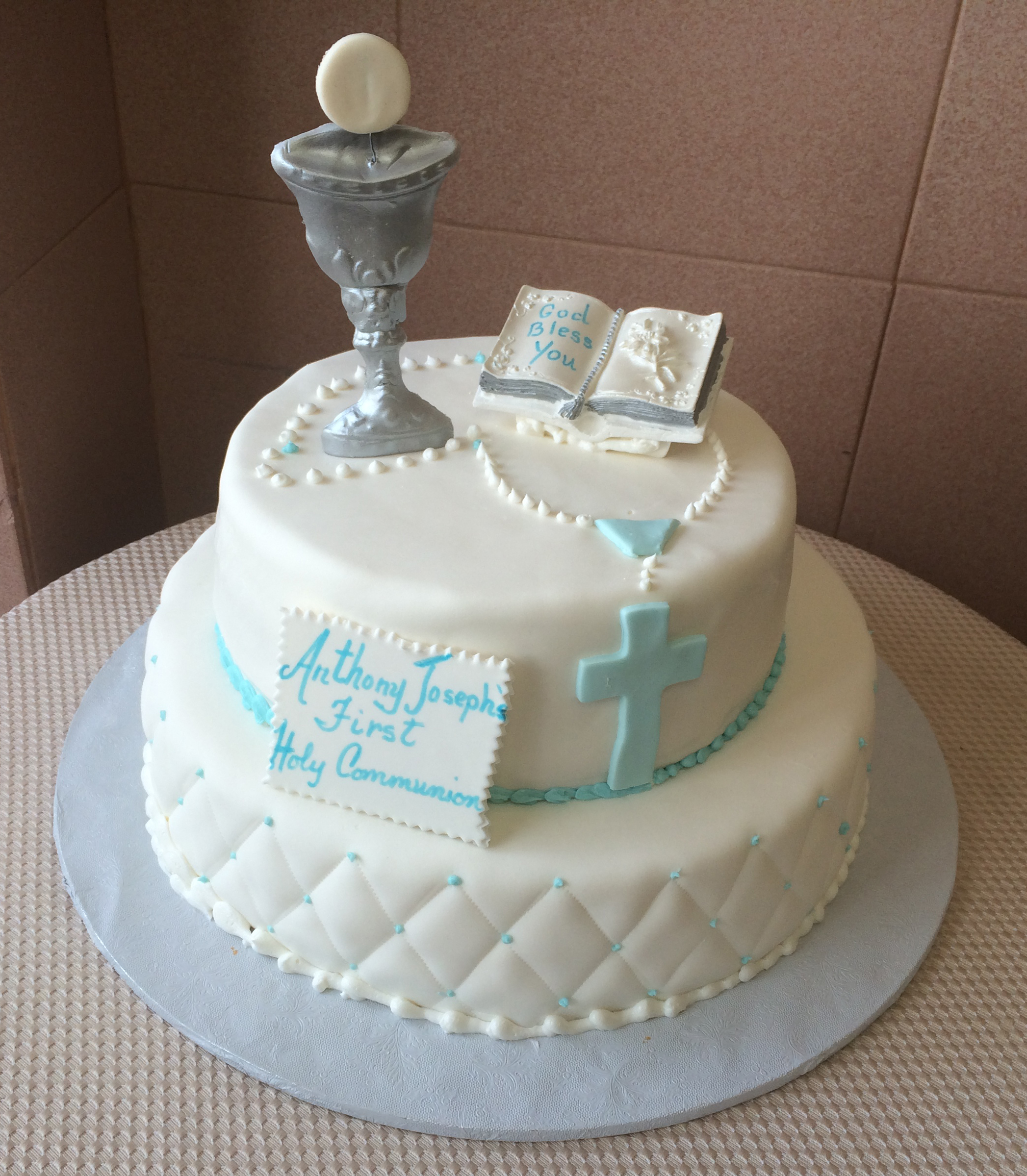 White Rolled Fondant Quilted with blue ribbon, blue rosary beads, standing silver chalice & ceramic keepsake bible
