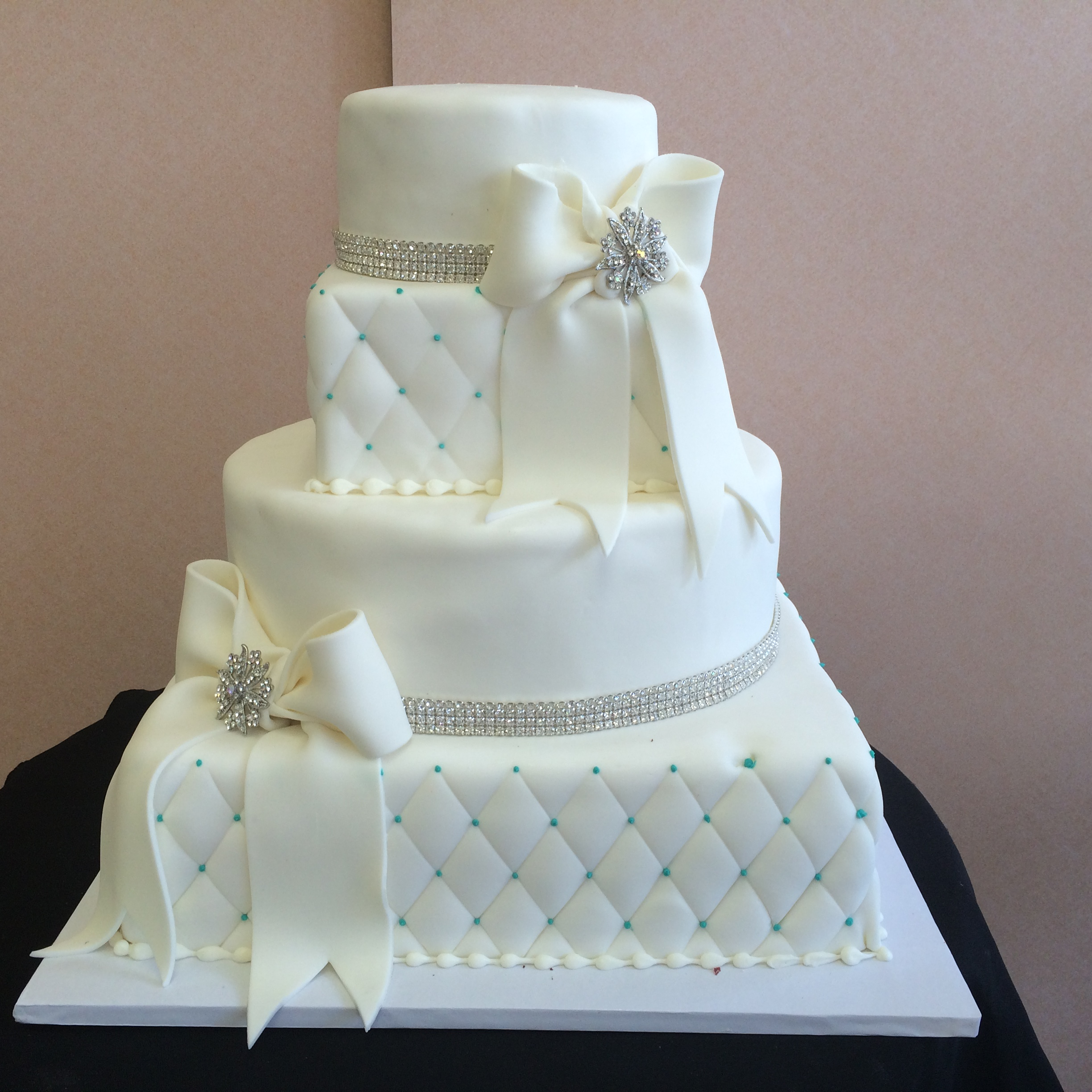 61 4 Tier in Rolled Fondant with Quilted Square Tiers, Round Tiers with Swarovski Crystals with Rolled Fondant Bow & Brooch