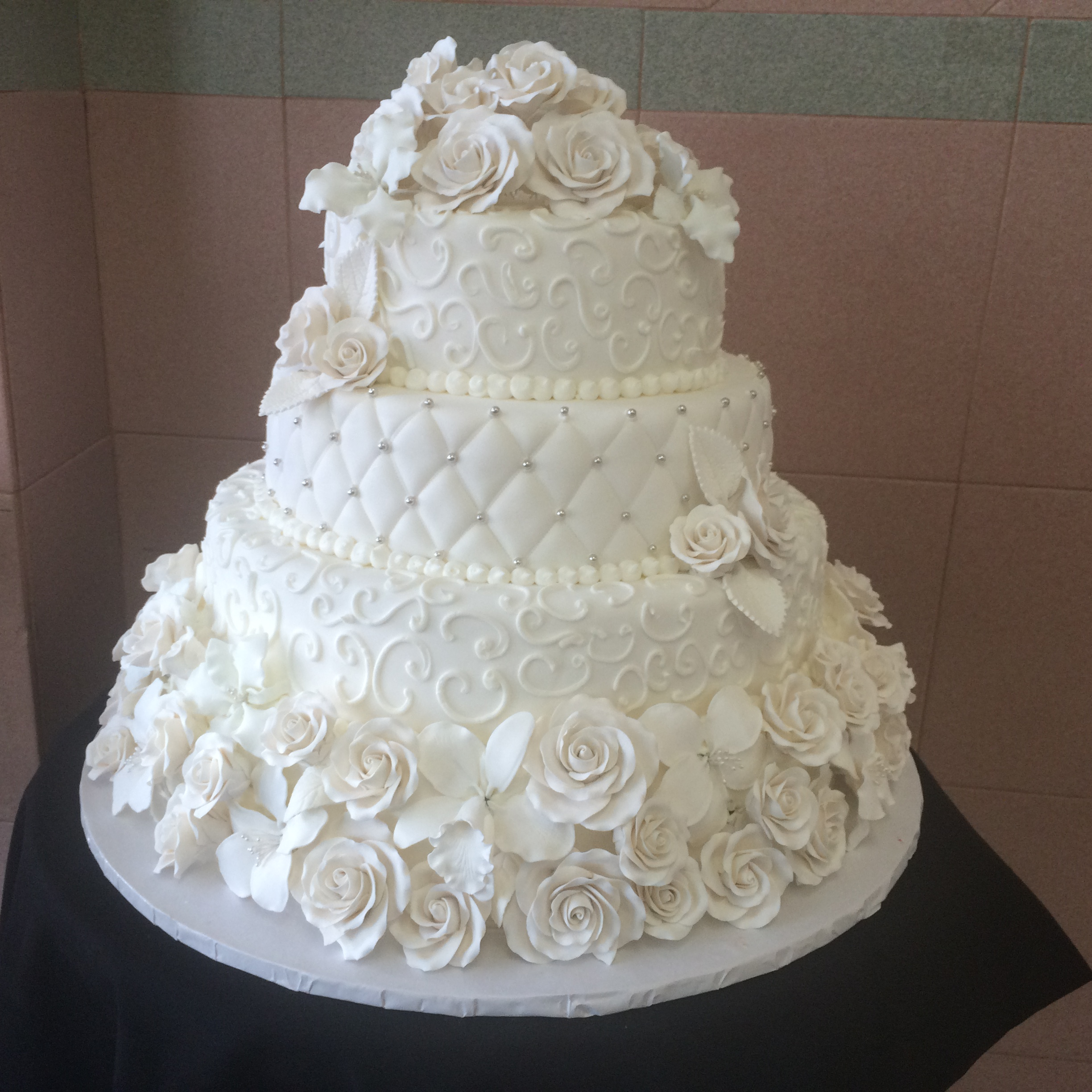 Assorted Rolled Fondant Flowers around 1st Tier. Scroll Work. Quilted with Silver. Scroll Work. Topped with Flowers.jpg
