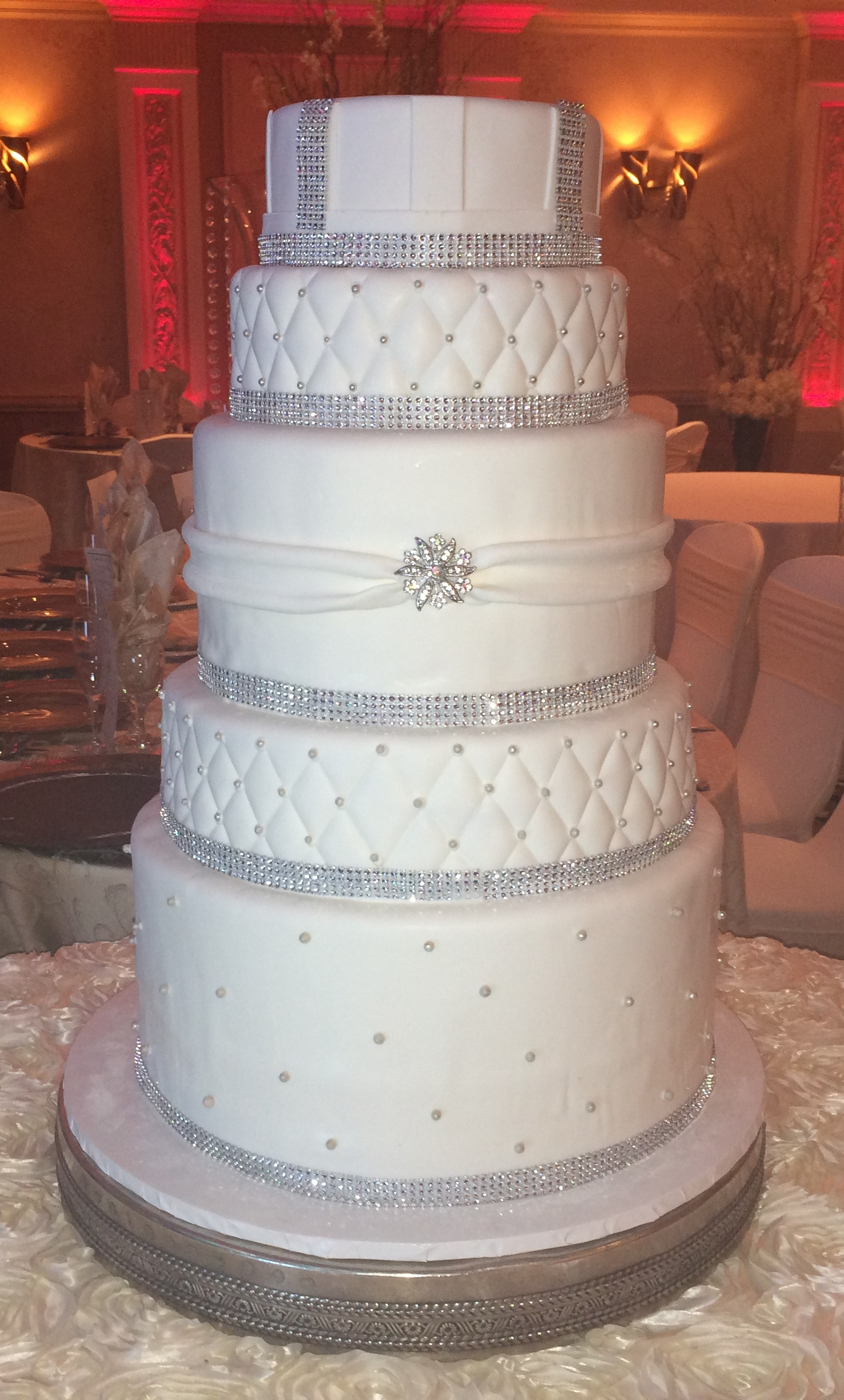 7Tier.Rolled Fondant. Doubled. Silver Pearls.Quilted.Doubled & Wrapped w Brooch. Quilted Silver. Rolled Fondant Stripes.Faux Crystals.jpg