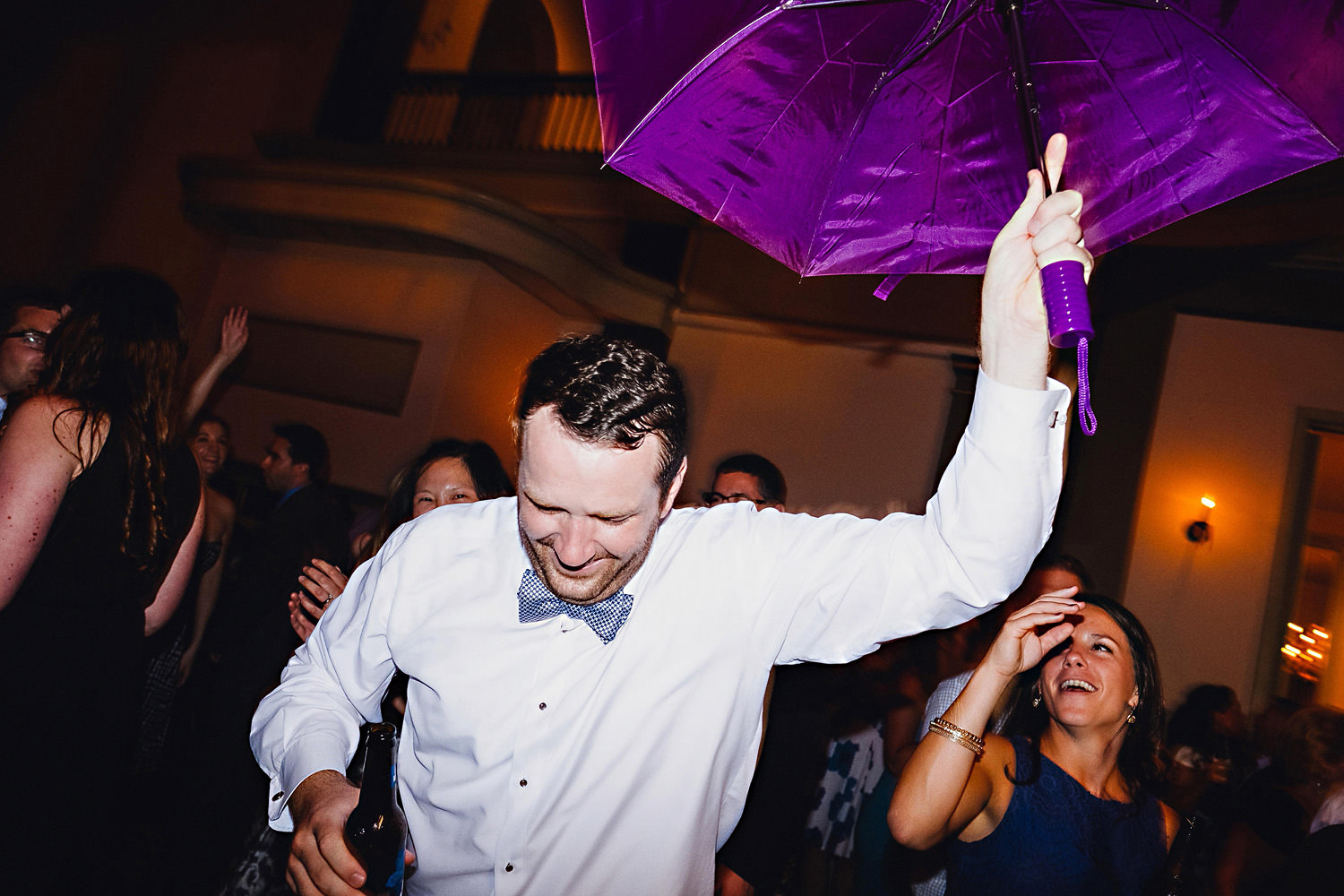A groom dances with umbrella.