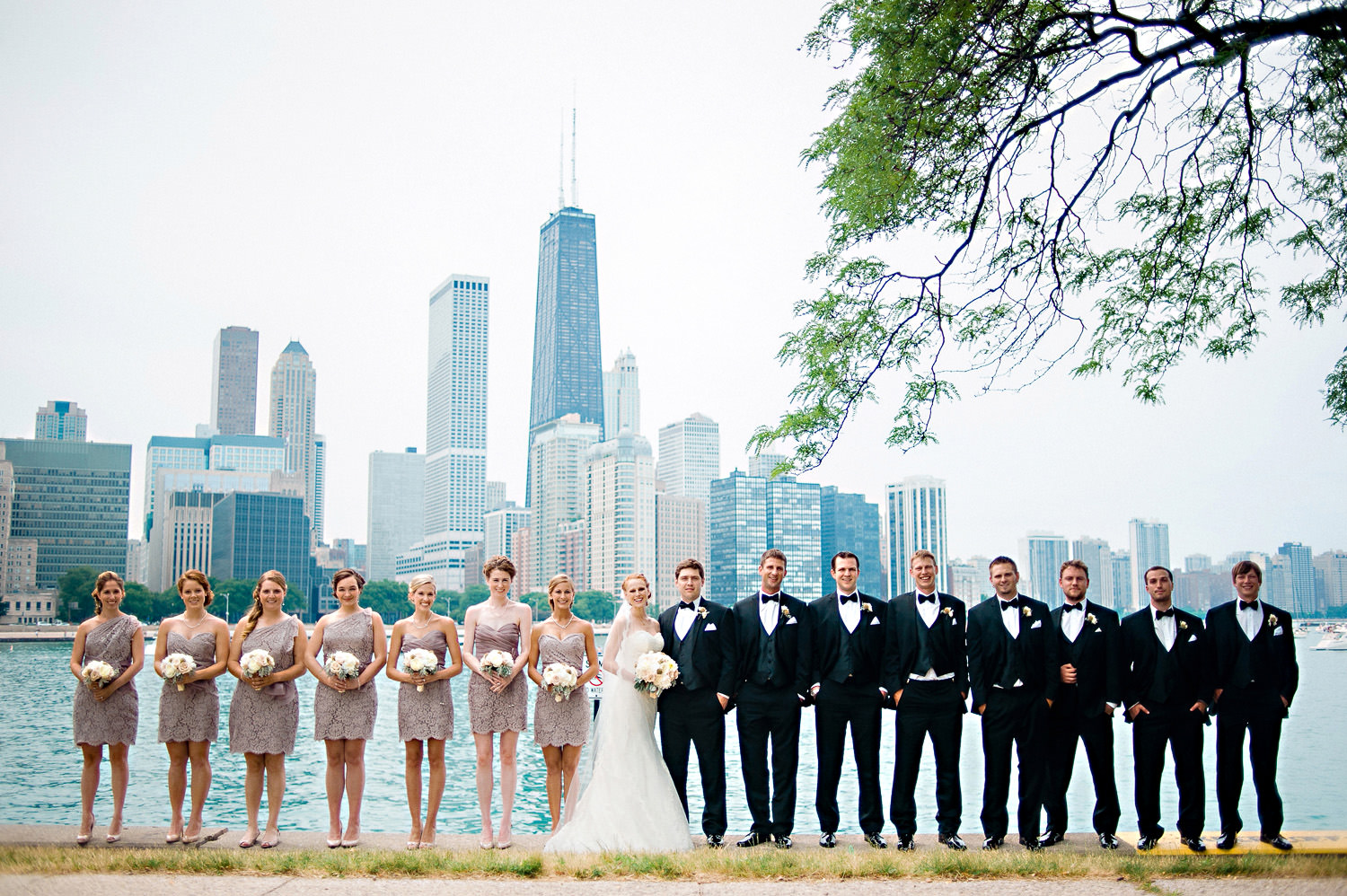 The bridal party poses for a photo in front of the Chicago Skyline.
