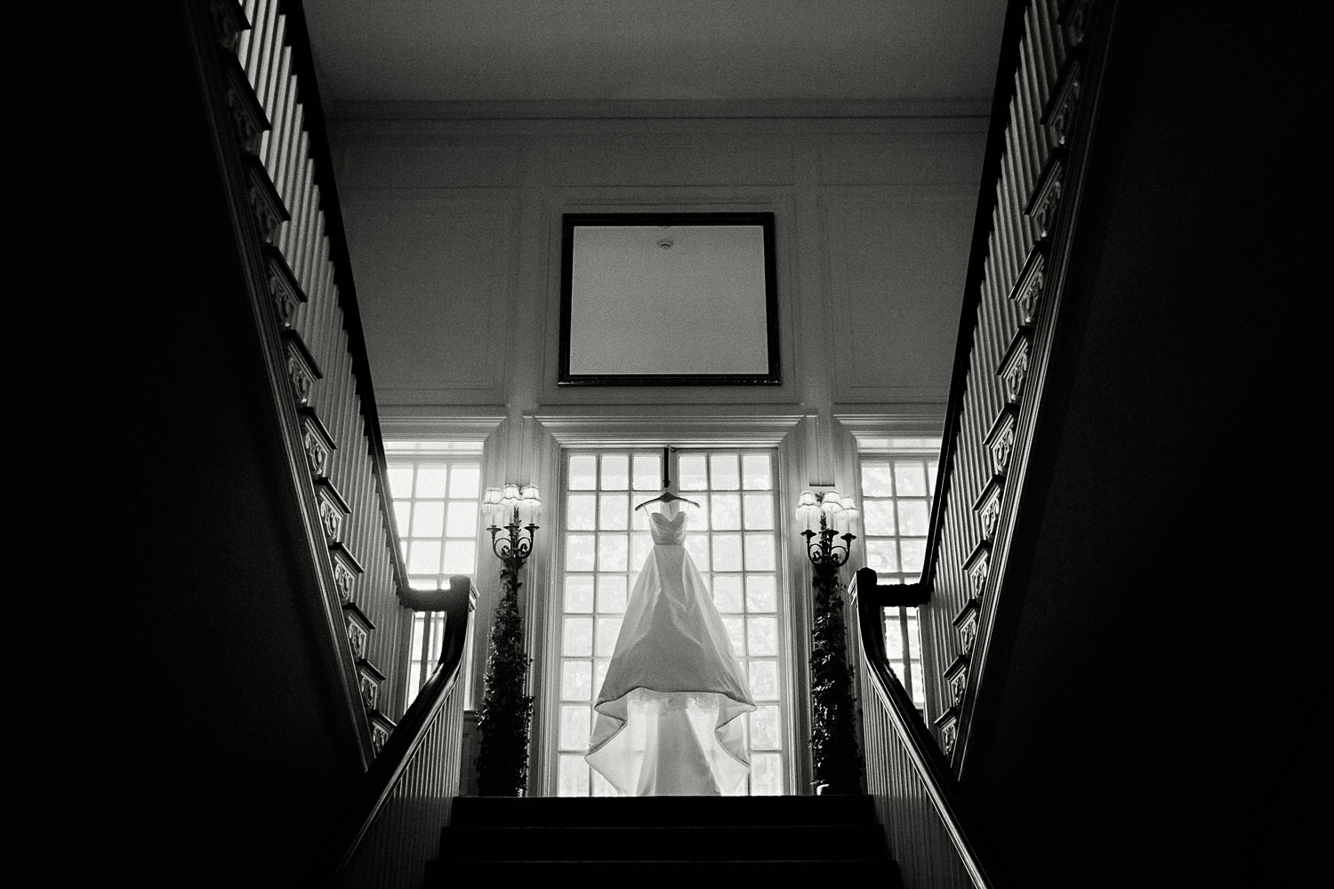 A wedding dress hangs in the window.