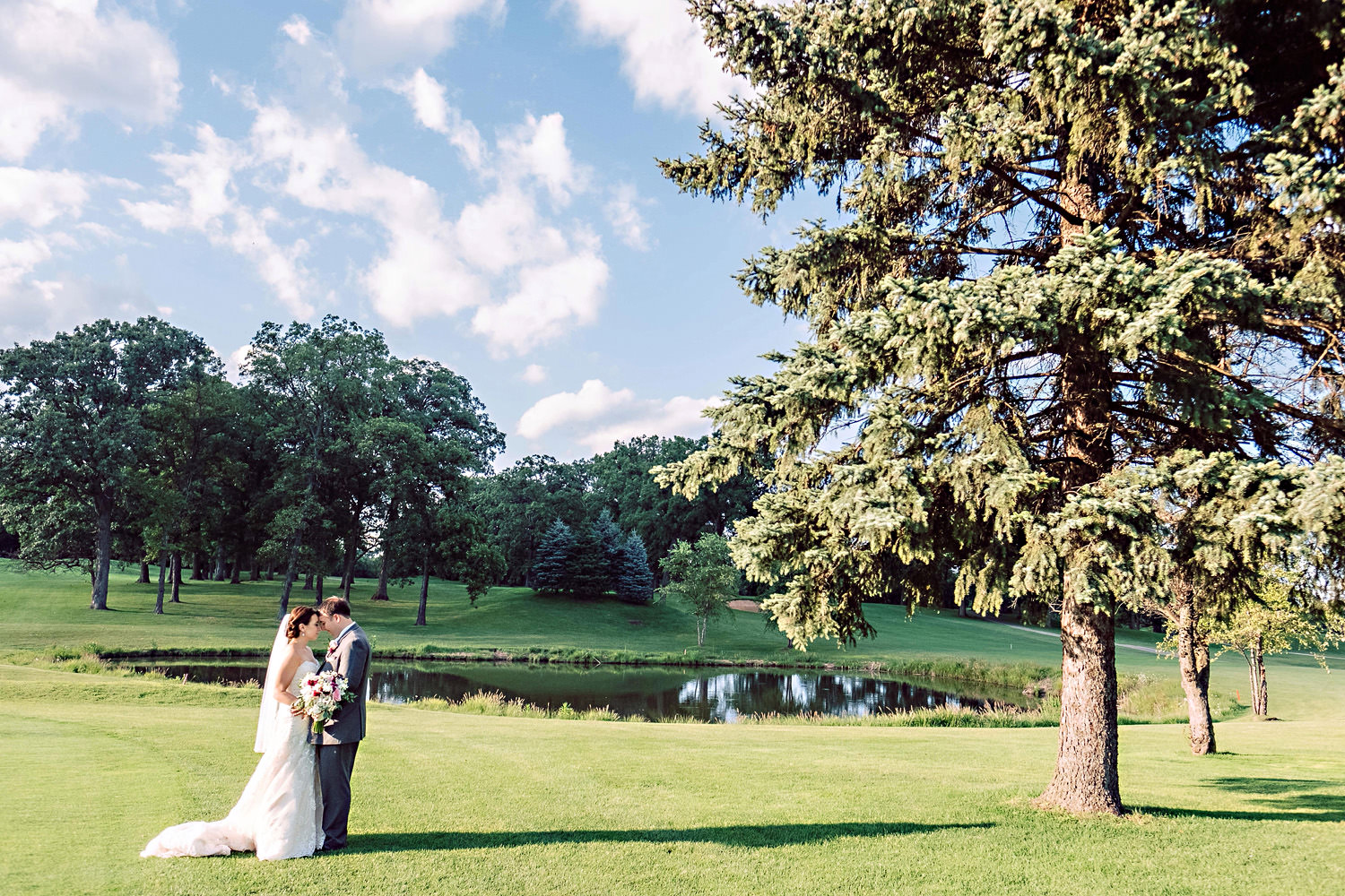 A bride and groom portrait on a golf course