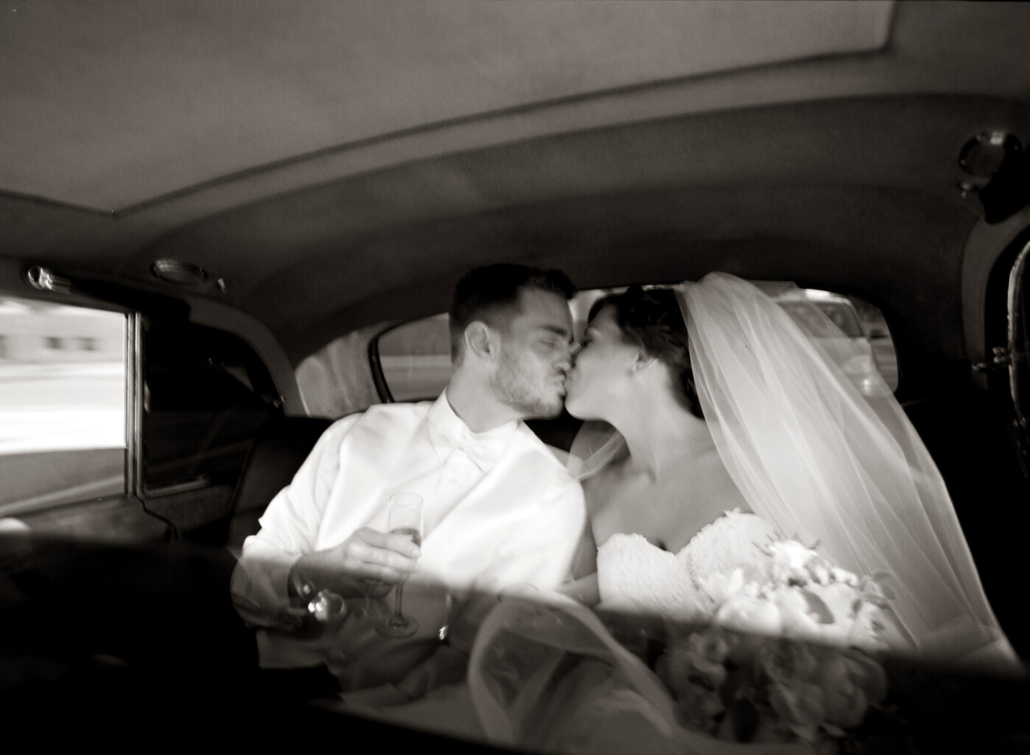 A bride and groom kiss in the back of the car.