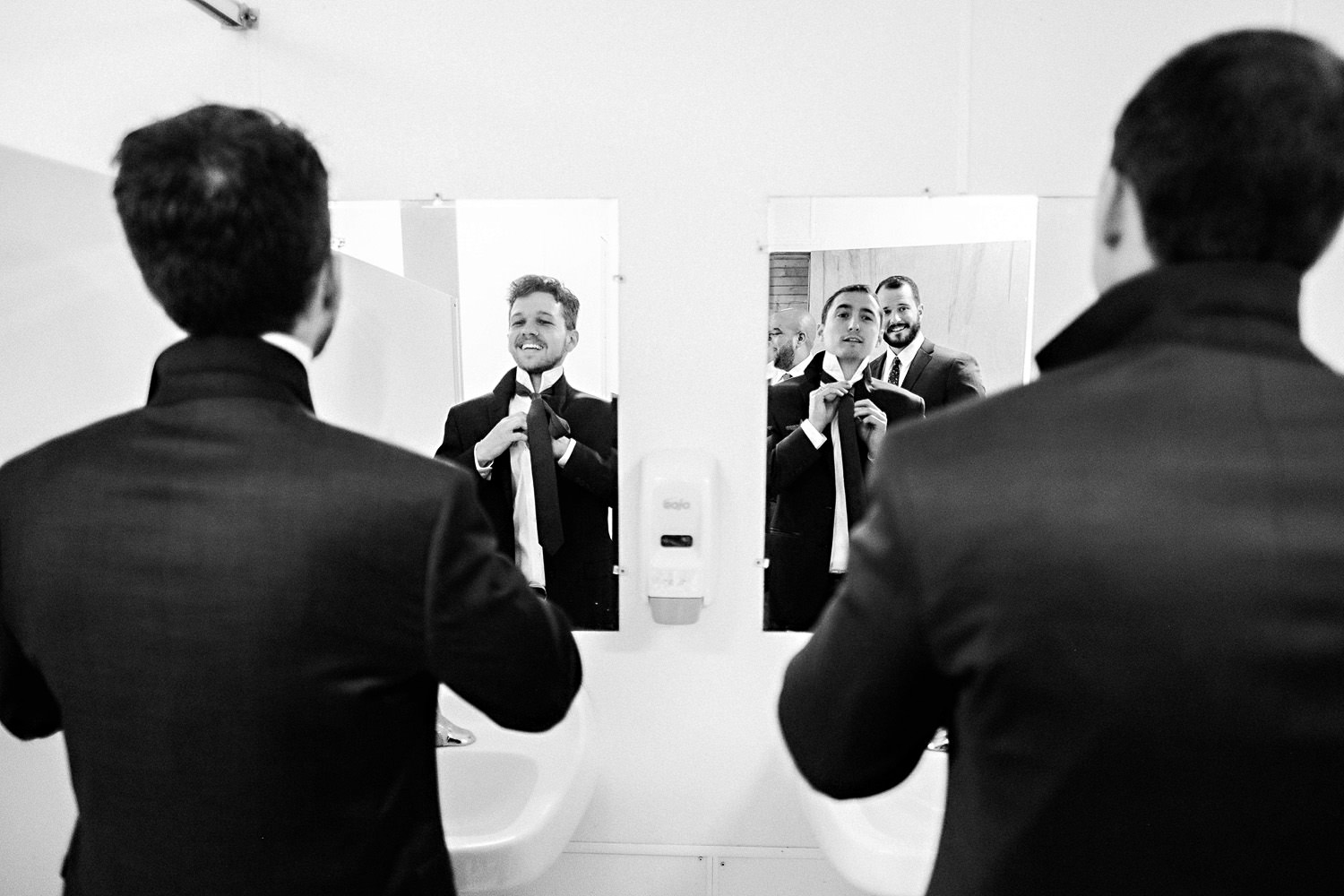 Groomsmen get ready in the bathroom mirror.