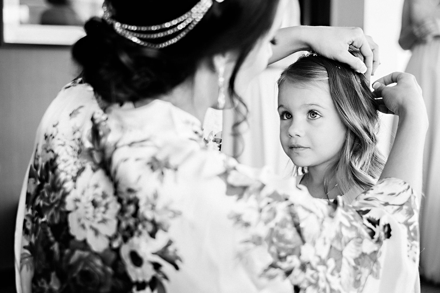 A bride fixes her daughters hair before the wedding