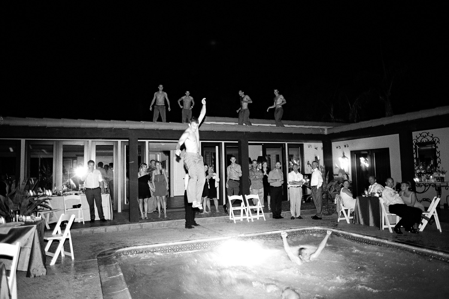 Groomsmen jump into the pool at the reception