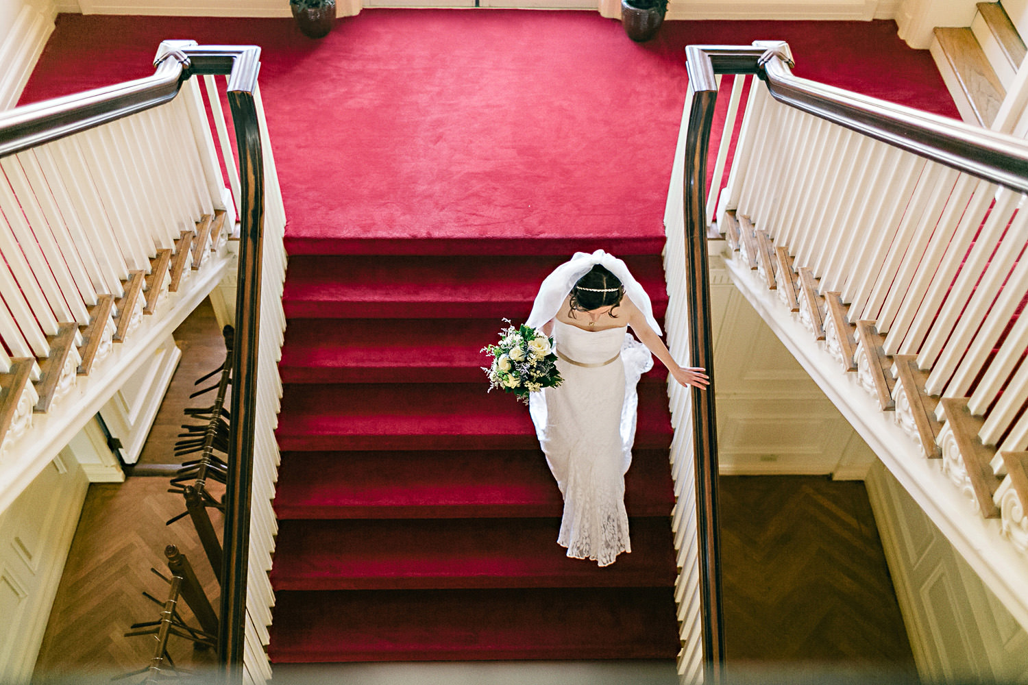 Bride walks down a red velvet staircase.