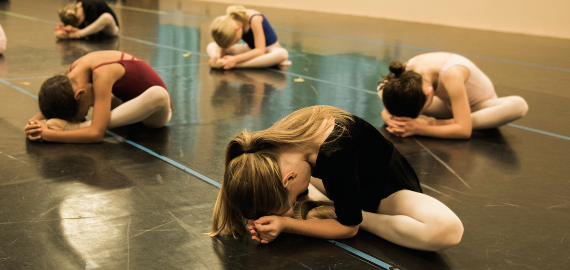 While these dancers are all doing the same stretch, notice that some dancers' knees are higher or lower and the feet are placed at varying distances from the body. Variation is crucial in healthy stretching.