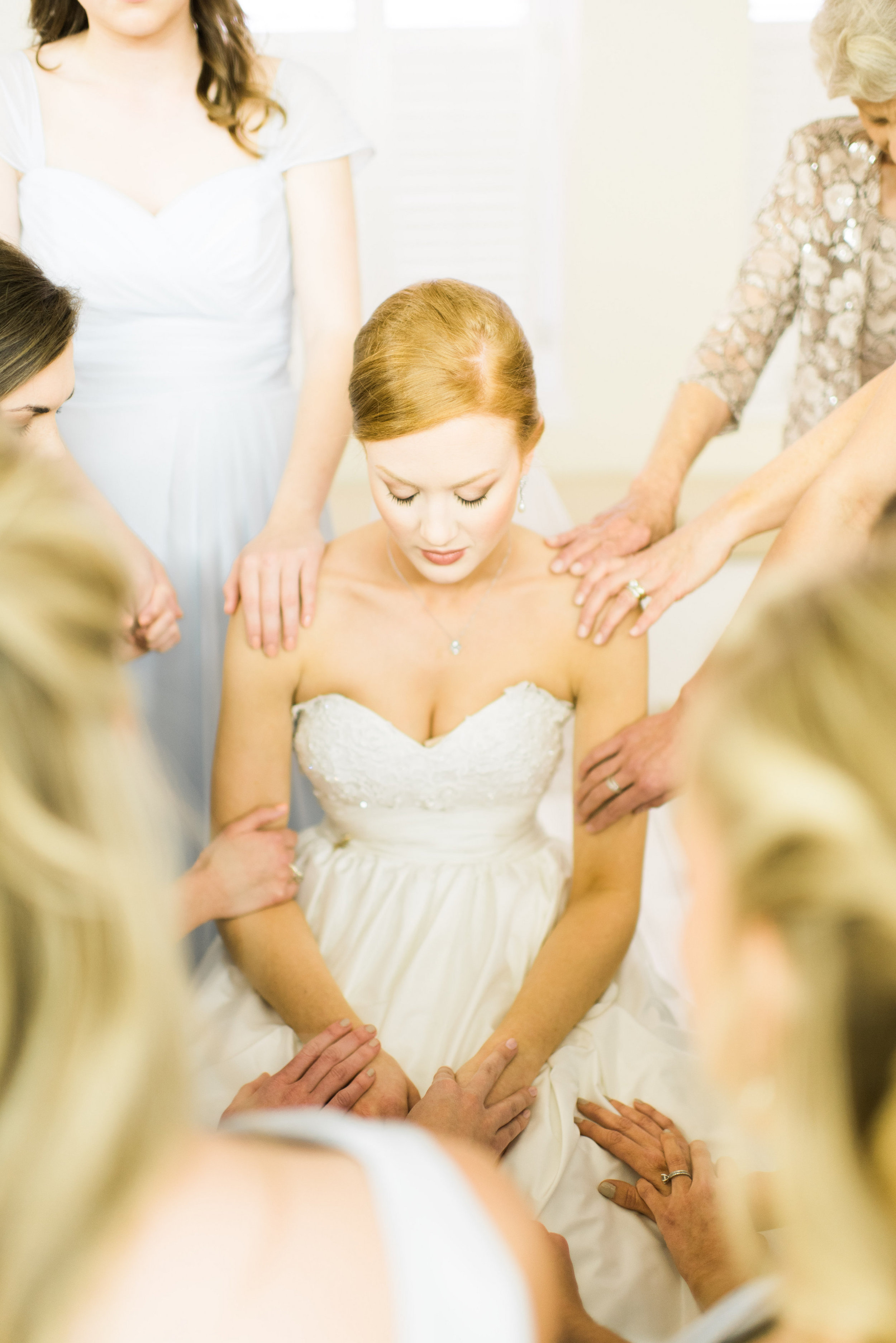 Moms and maids praying over the bride