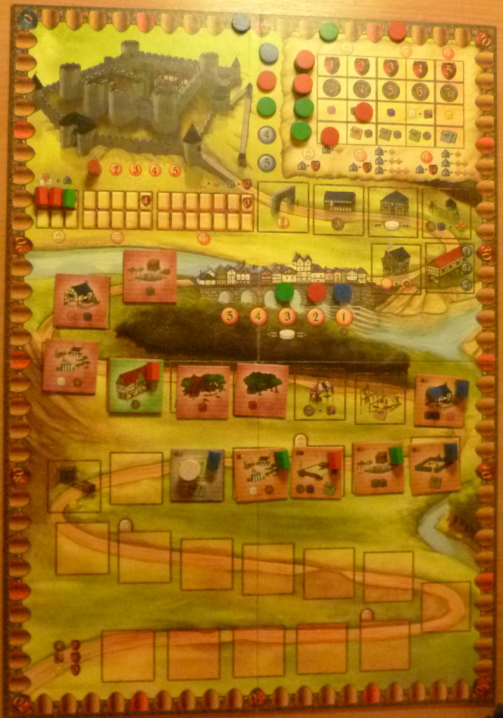 "The board in Caylus with the path and a few buildings (coloured houses show player owned buildings), top left Castle and top right ""Favour"" tracks."