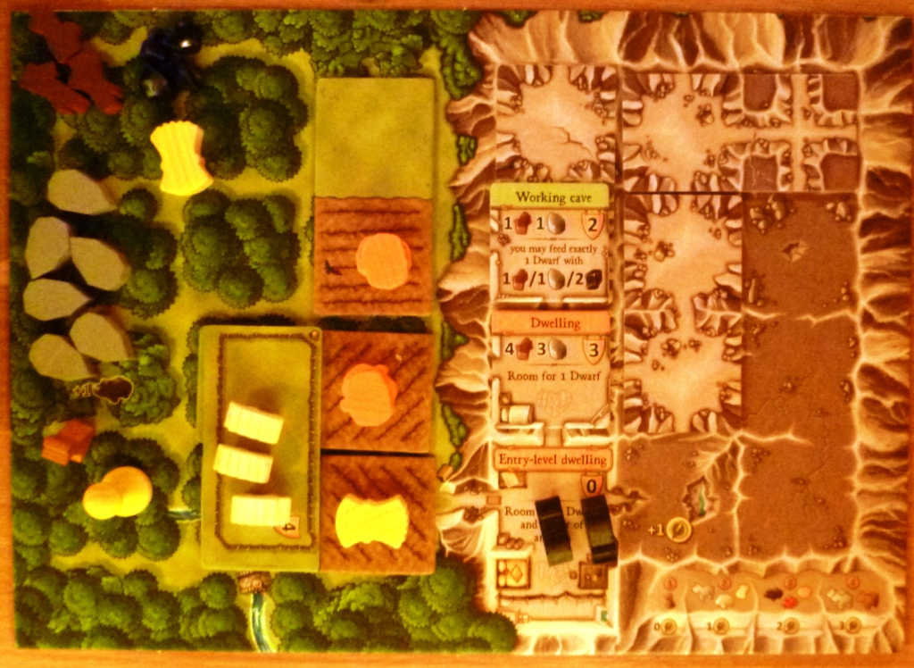 Player board in early stages of game, with some sheep in a pasture, 2 pigs in a cave and wheat and vegetables planted in fields