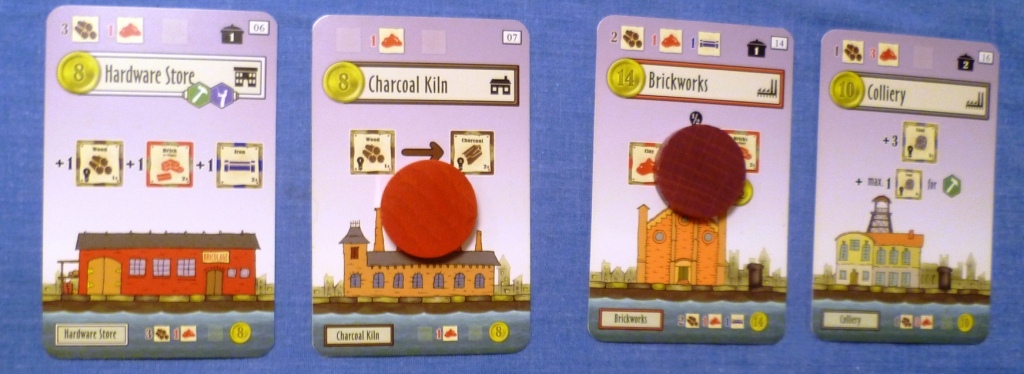 Four of the building cards, Red has converted wood into charcoal, when the charcoal kiln was built it cost 1 clay to build.