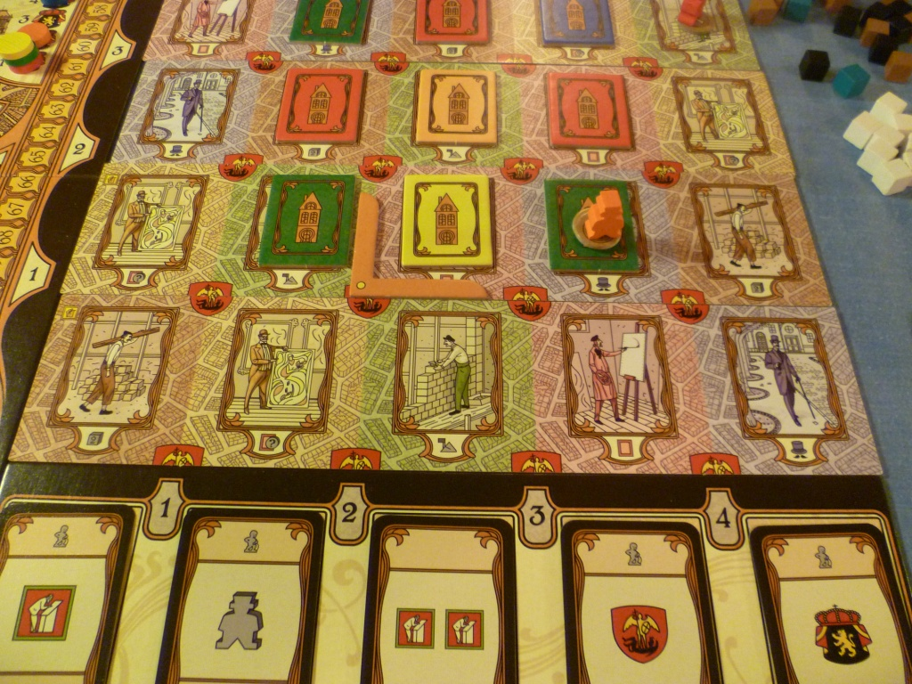 """Mid-game. This part of the board showing one of the worker placement areas with some buildings erected and at the bottom of the screen bonus cards for column control. The """"L"""" shape indicates the area of the board currently in play."""
