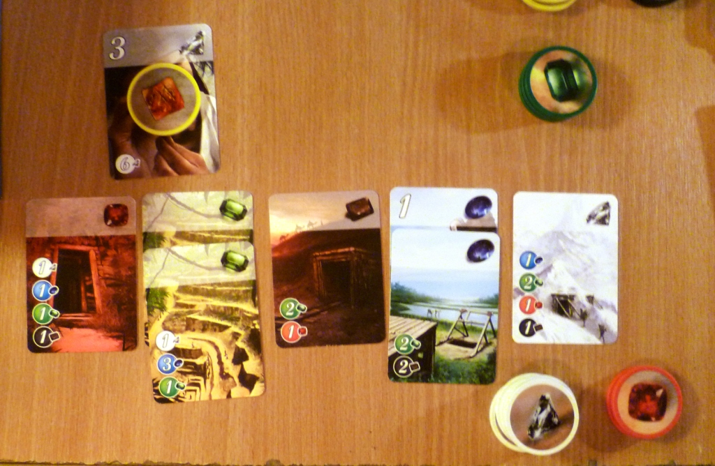 A players collection of cards in Splendor with 4 points of the 15 needed.