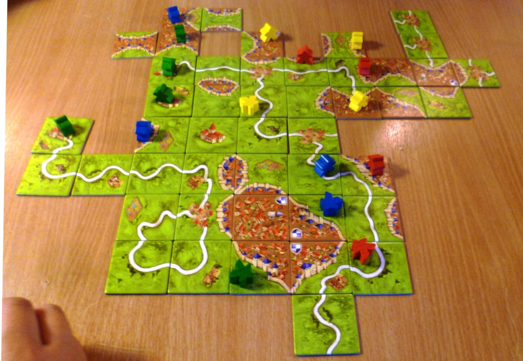 Carcassonne - Blue on the road feature looking to on the right while yellow has a stake in several cities at the top