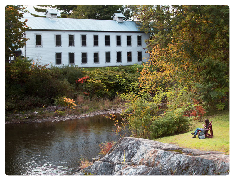 Set in an autumn landscape, a person sits in a red Adirondack chair beside the banks of the Gihon river across from the Maverick Studios building