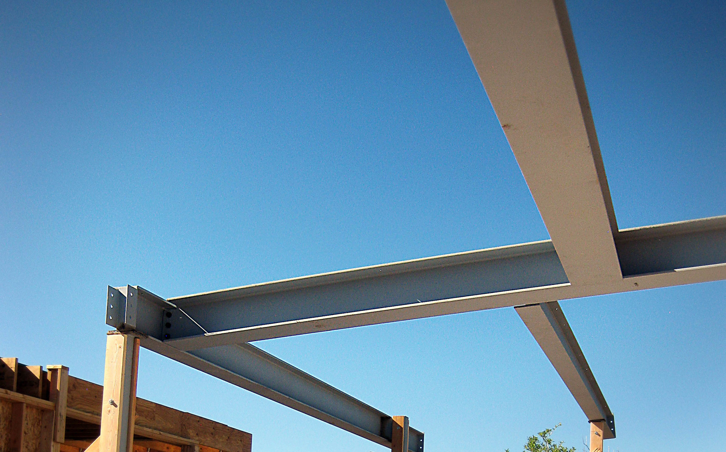 structural steel beams of a contemporary style home viewed during a site visit in a project's construction observation phase