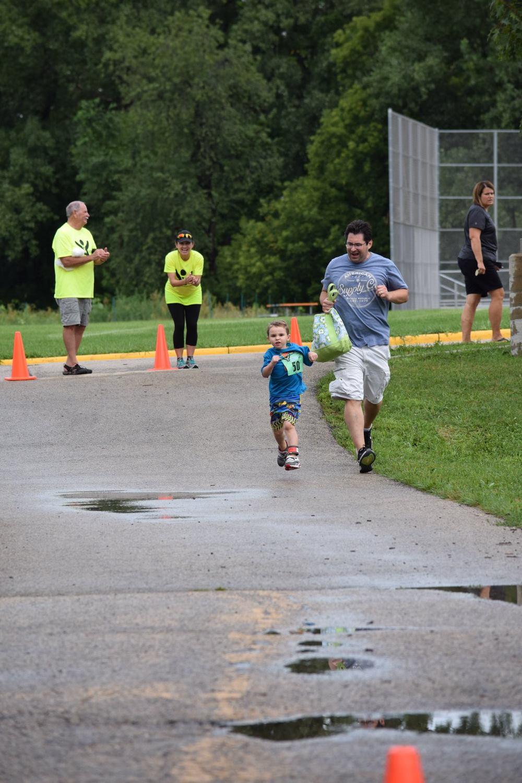 Man running alongside a little boy.
