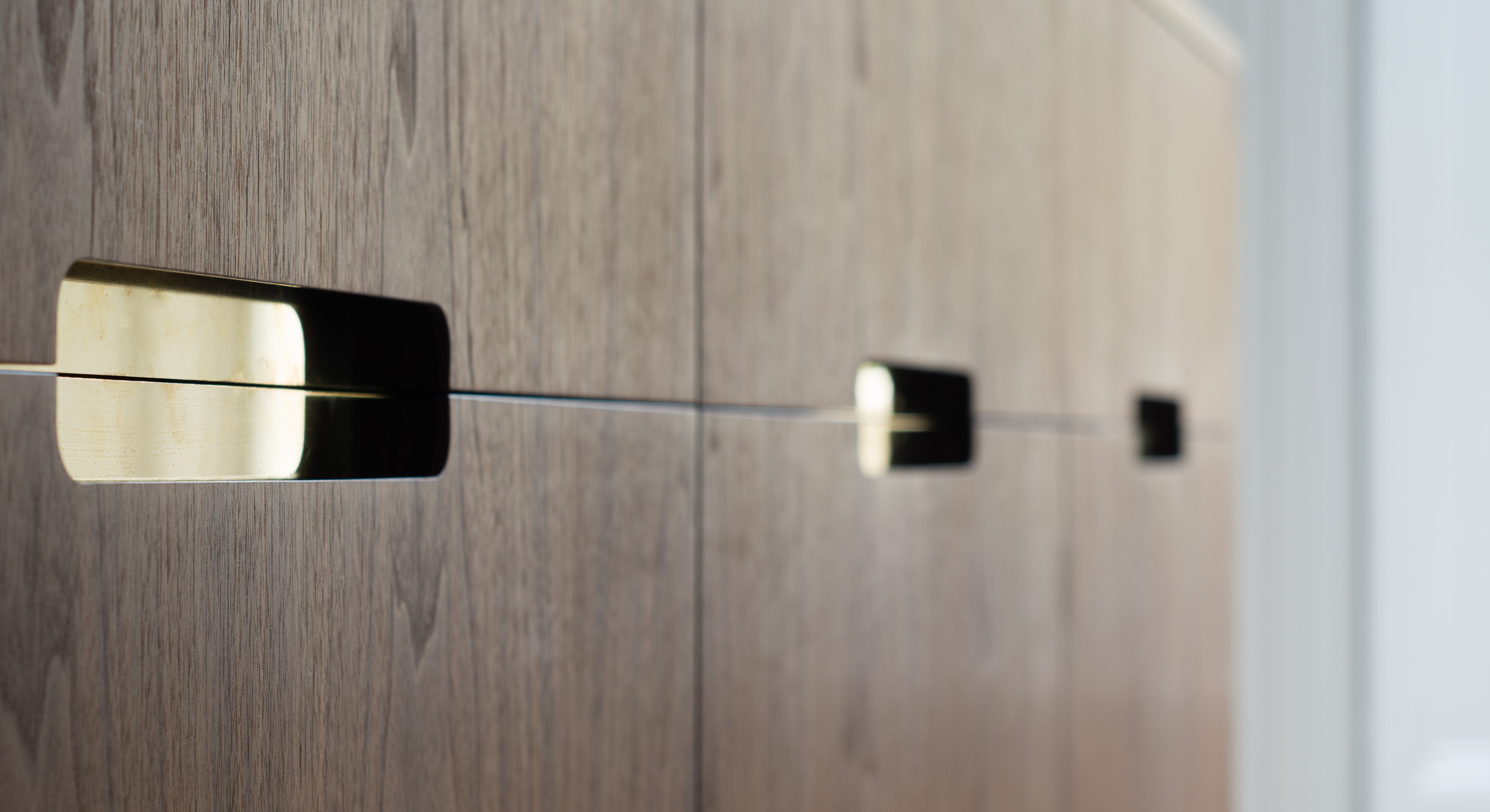 Bespoke freestanding furniture - routed finger pull detail showing polished brass reveal