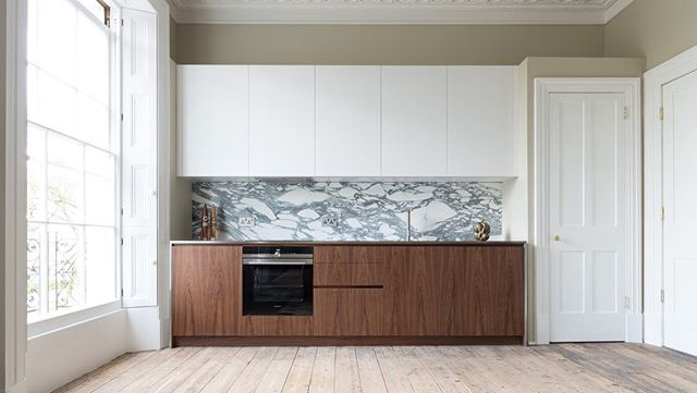 We designed and built this bespoke kitchen for a great client in this beautifully and sensitively restored Cheltenham townhouse. To achieve proper visual separation between the kitchen and the traditional mouldings of this Georgian building we specified a mitred stainless steel work surface to wrap around our walnut cabinetry.  This kitchen was constructed using custom grain matched walnut veneered fronts, white spray lacquered wall units and cover panels, a mitred stainless steel work surface, integrated LED lighting and a stunning Arabescato marble back splash.