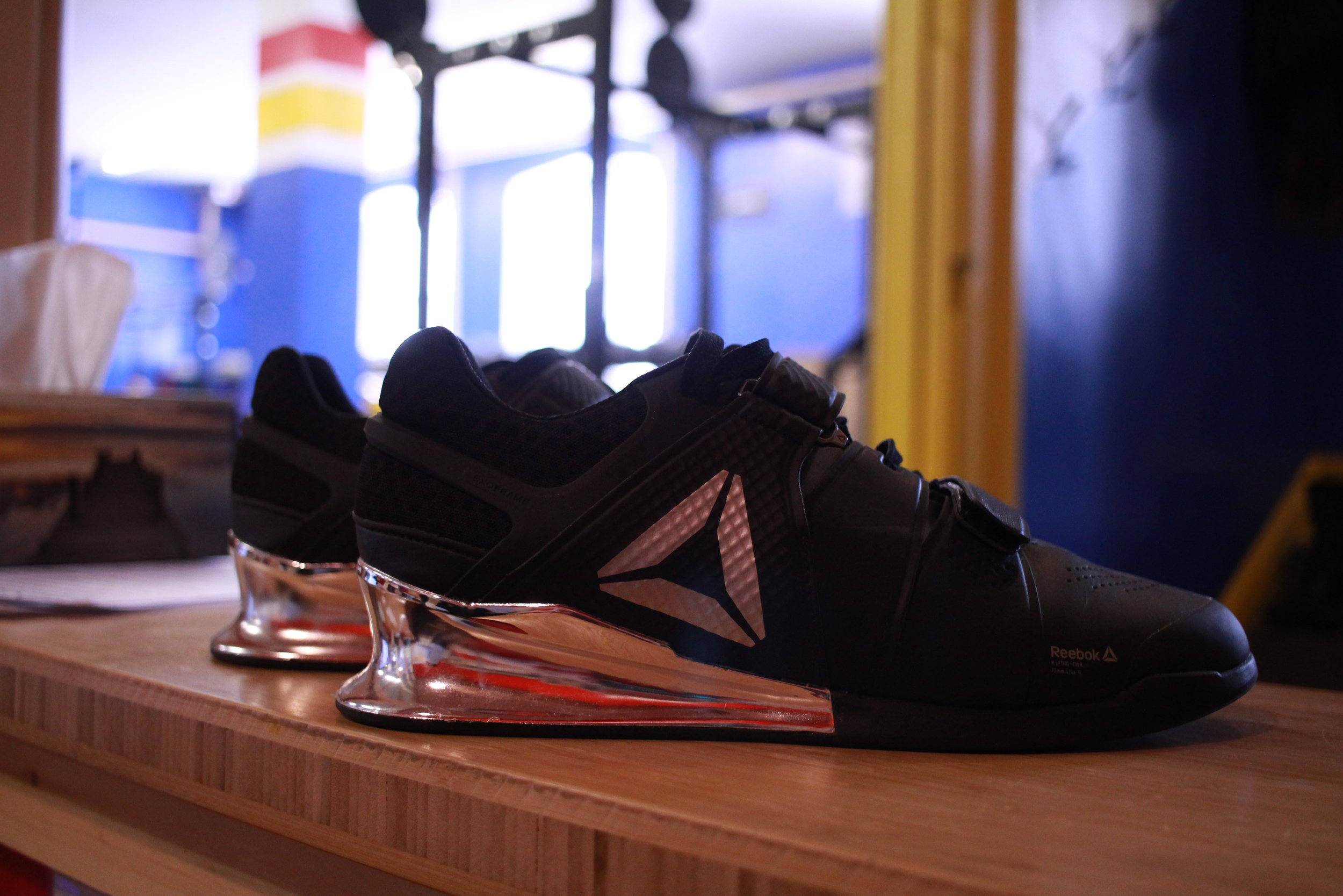 Weightlifting Shoes (LIFTERS)  Regular running and training shoes often have minimal soles. They are built to absorb the force associated with each step as it is applied. When weightlifting (front, back or overhead squatting; performing the Clean and Jerk or the Snatch), you want to be able to transfer more force into the ground, increasing your ability to pull the bar higher or drive out of the bottom position of the squat. Weightlifting shoes are thus designed with a still sole and a raised heel. The raised heel assists in the range of motion of the ankle: with the ankle slightly raised, it is easier to sit back into the squat rather than leaning forward.