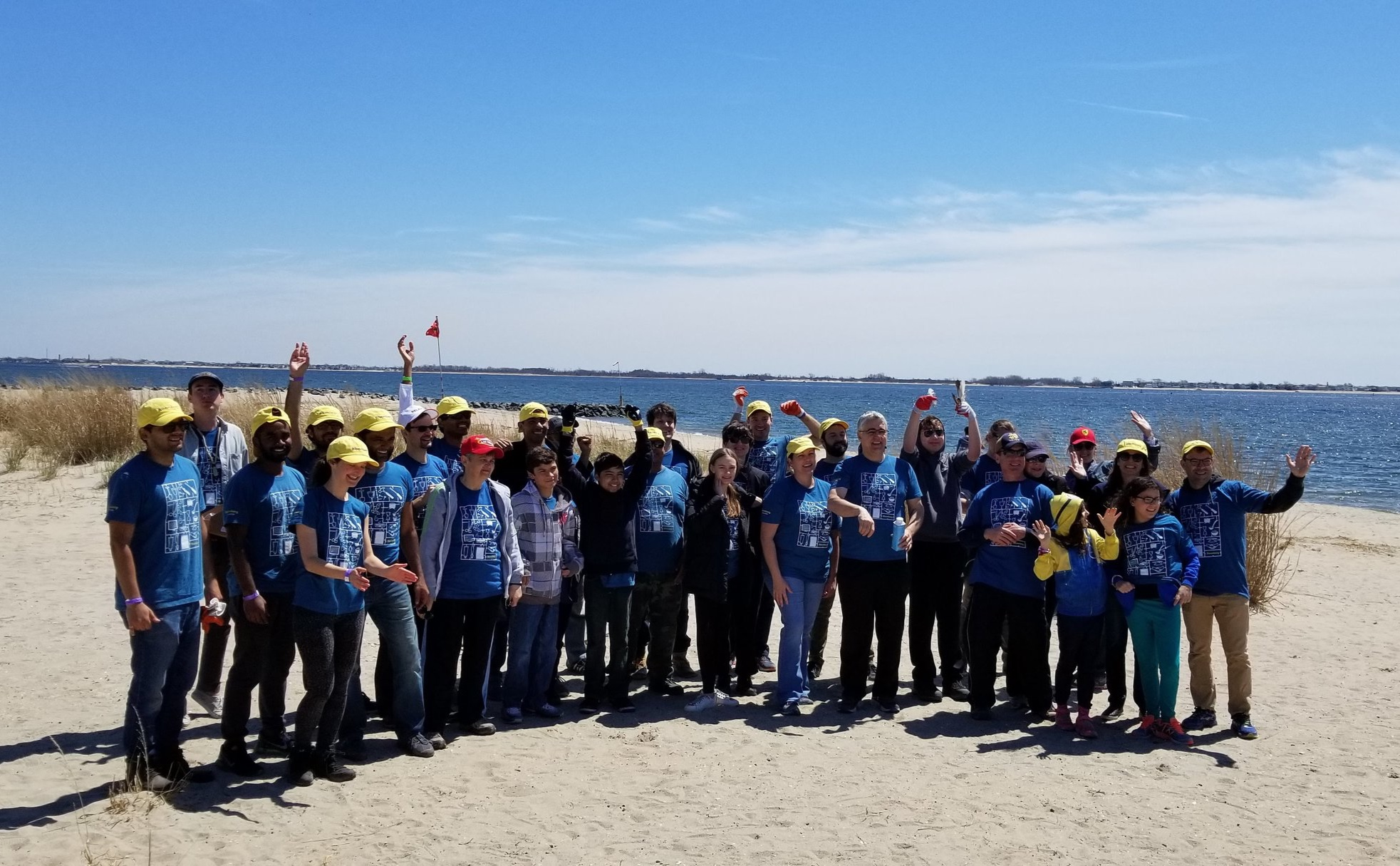 Bloomberg volunteers and their families remove marine debris and trash from Plumb Beach shoreline on Earth Day, 2018.