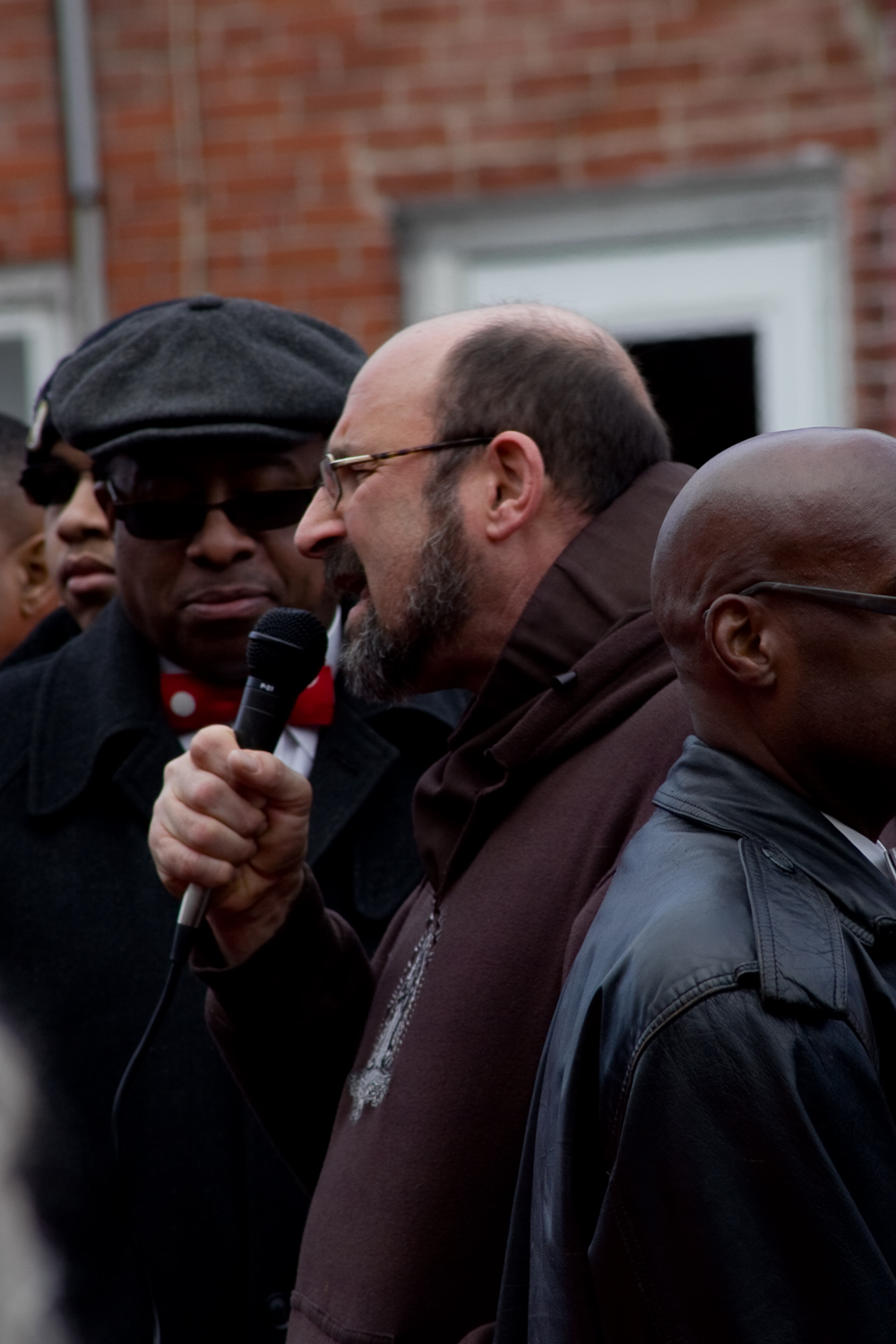 Fr. Chris Posch takes the microphone to lead a prayer in English and Spanish at the Martin Luther King Jr. Day march in Wilmington, Delaware on January 19, 2015