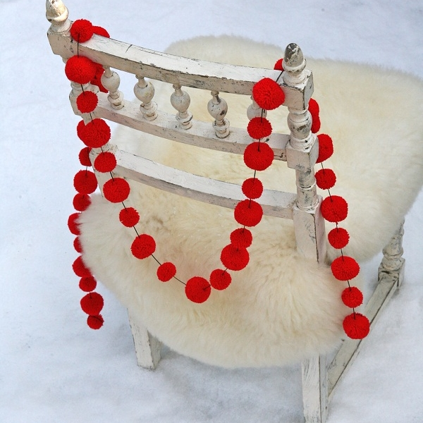 Red wool PomPom garland on back of chair by PomPOm galore £16.jpg