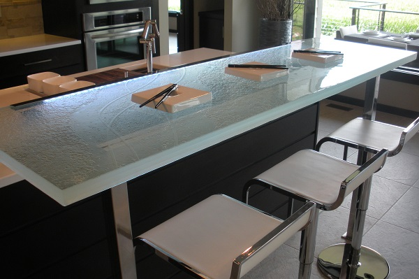 """The above raised glass countertop features a custom surface texture, 1 ½"""" thickness, LED underlighting, and is being attached by a stainless steel bracket that is extending to the floor (stand -off brackets are also available which attach to the surface and not the floor)"""